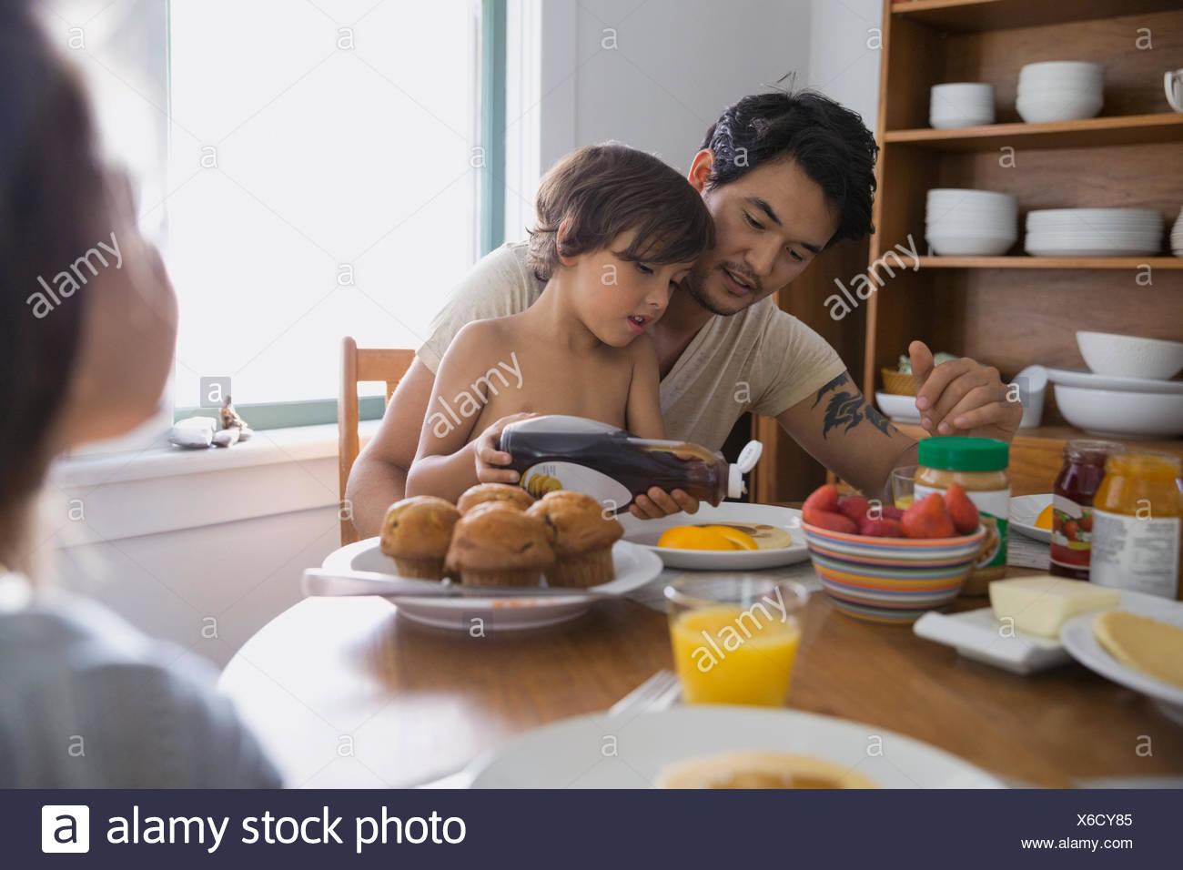 Vater Sohn Gießen Sirup auf Pfannkuchen beobachtete Stockbild