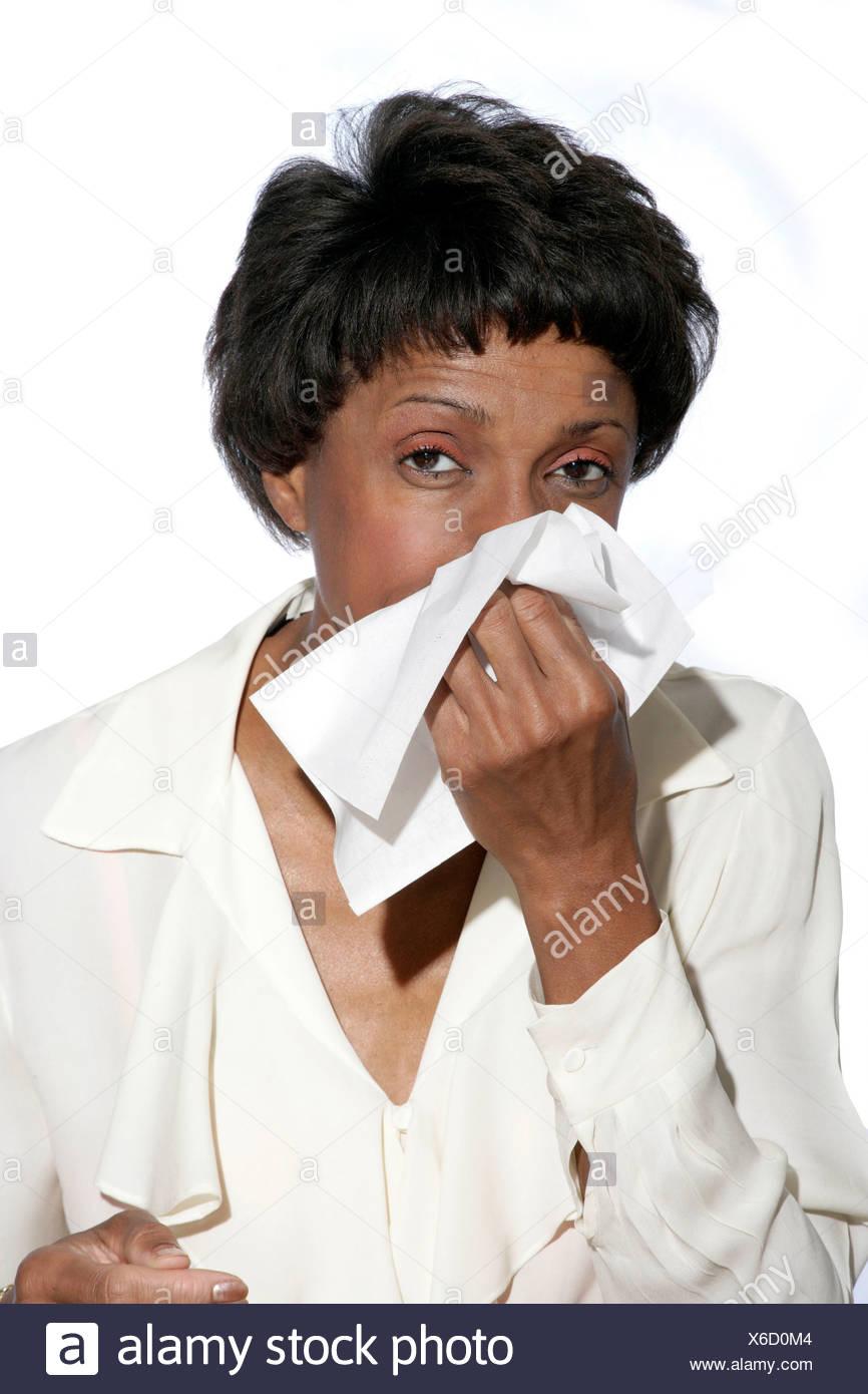 Frau bläst ihre Nase mit Gewebe. Stockbild