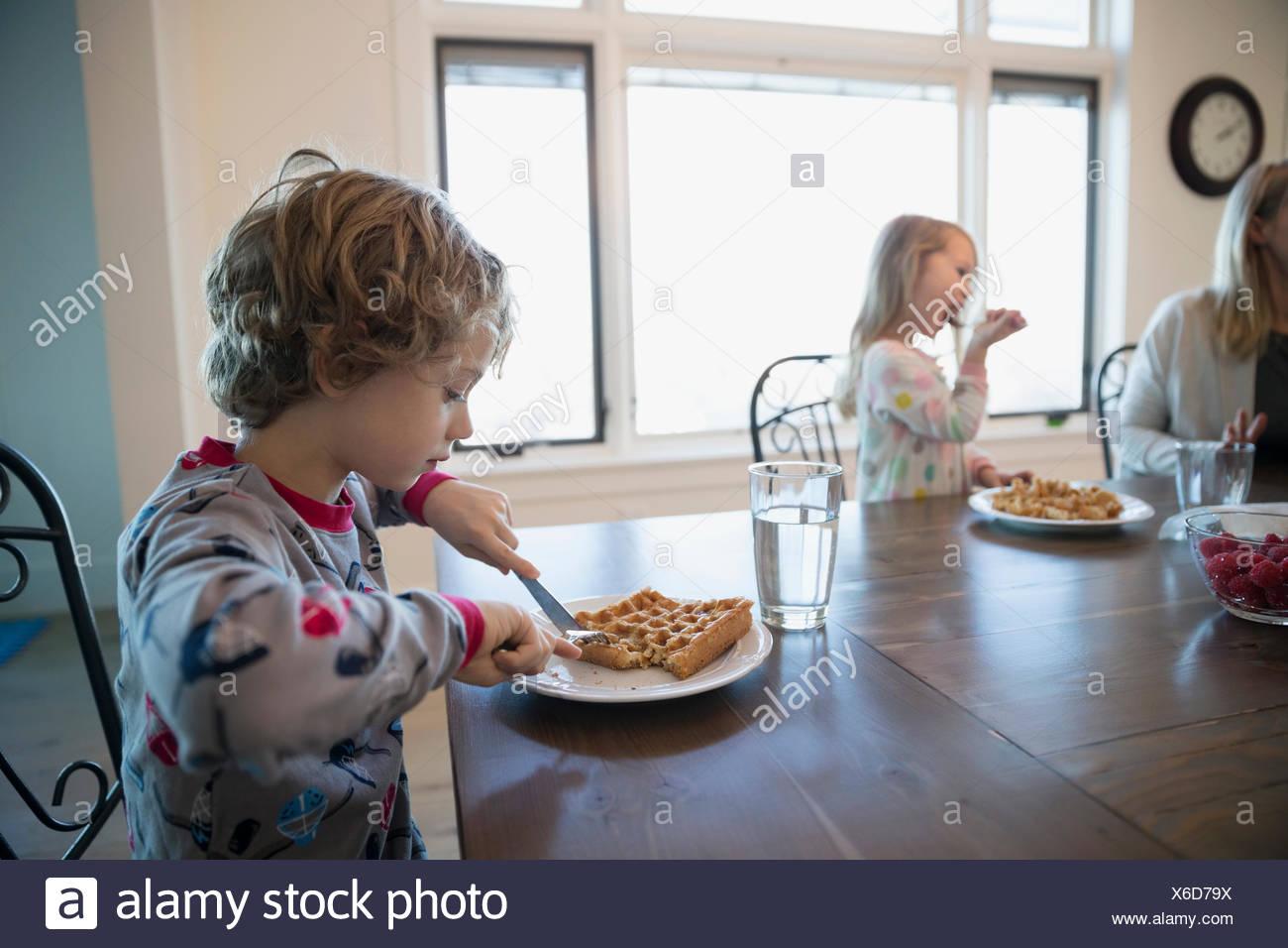 Junge essen Waffeln am Frühstückstisch Stockbild