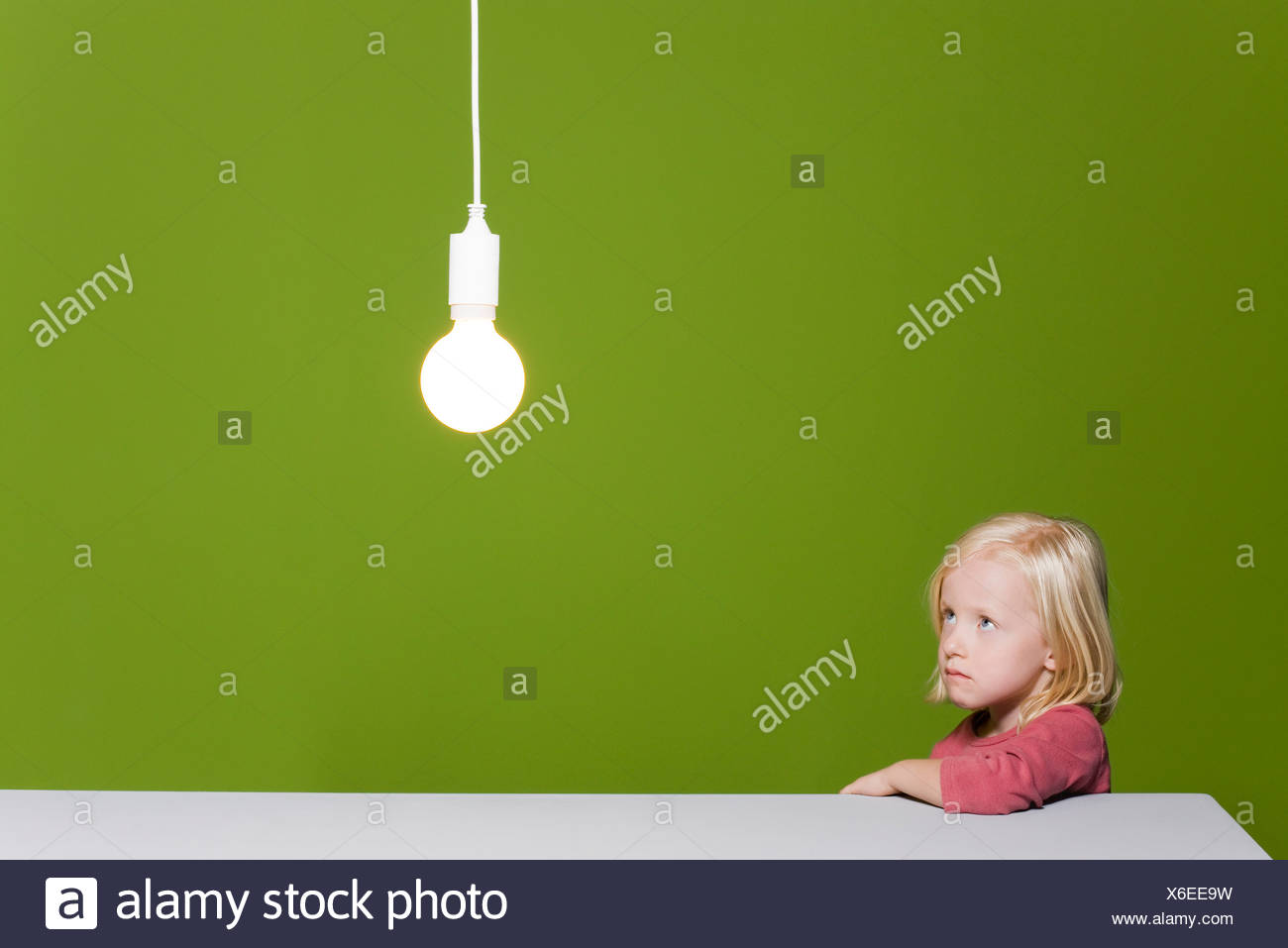 Kleines Mädchen beißen Lippe blickte mit Besorgnis leuchtende Glühbirne über Kopf ausgesetzt Stockbild
