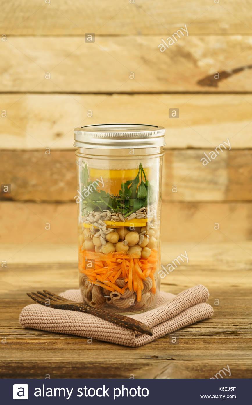 Veganer und vegetarischer Salat zum Mitnehmen im Glas mit Vollkornnudeln, gestifteten Möhren, Kichererbsen, gelben Zucchini, Sonnenblumenkernen, Peter Stockbild