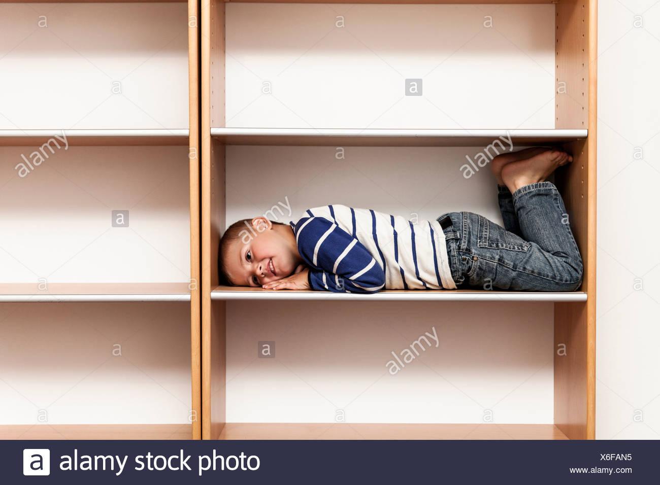 Gesamte Länge der verspielte junge im leeren Regal zu Hause liegen Stockbild