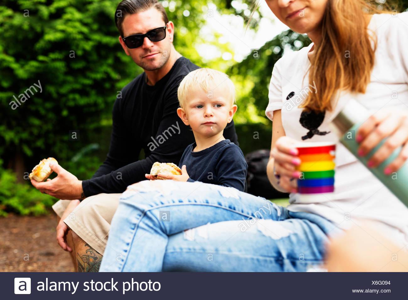 Eltern und Sohn mit Essen im park Stockbild