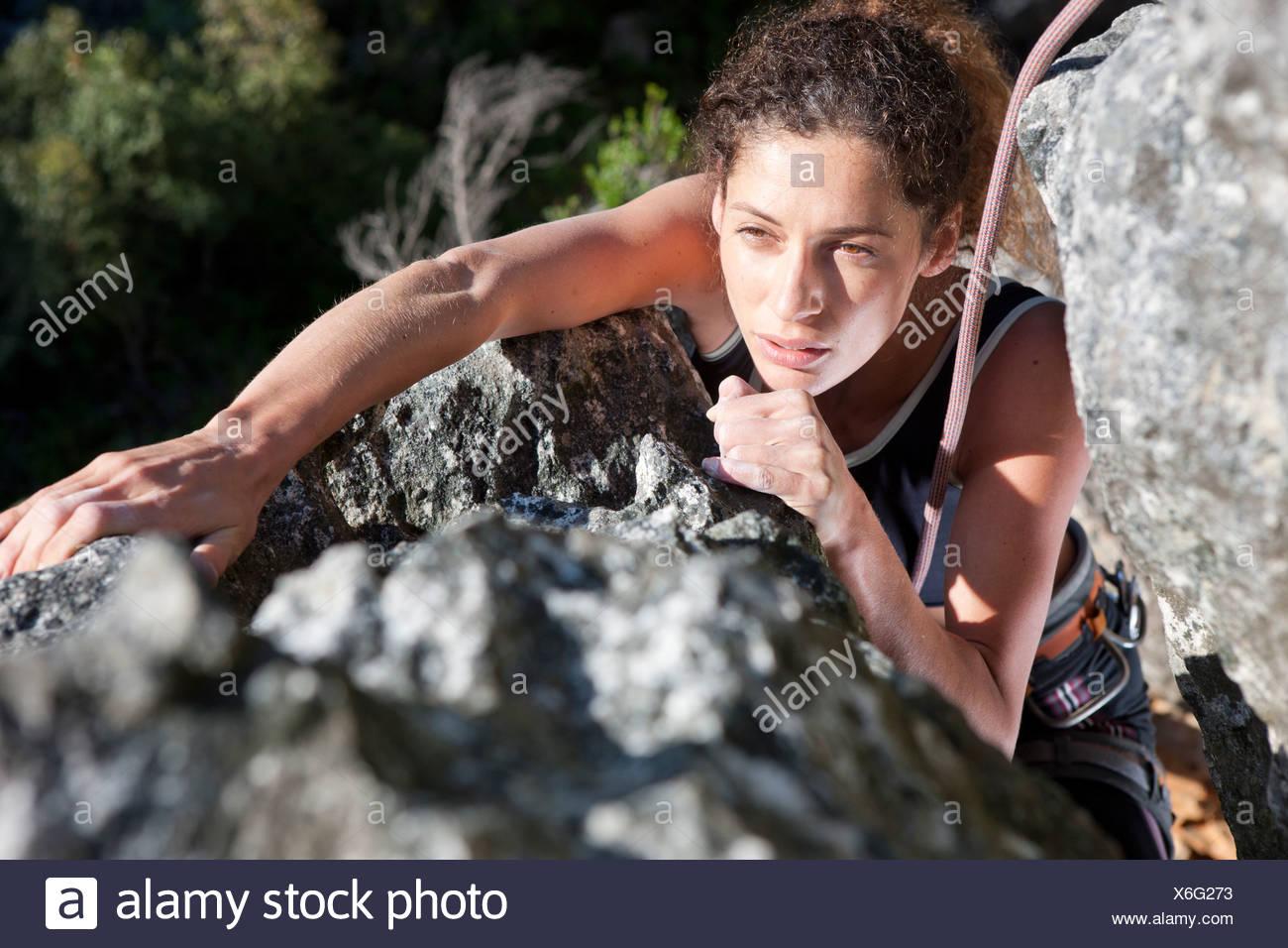 Junge weibliche Kletterer Felswand hochschieben Stockfoto