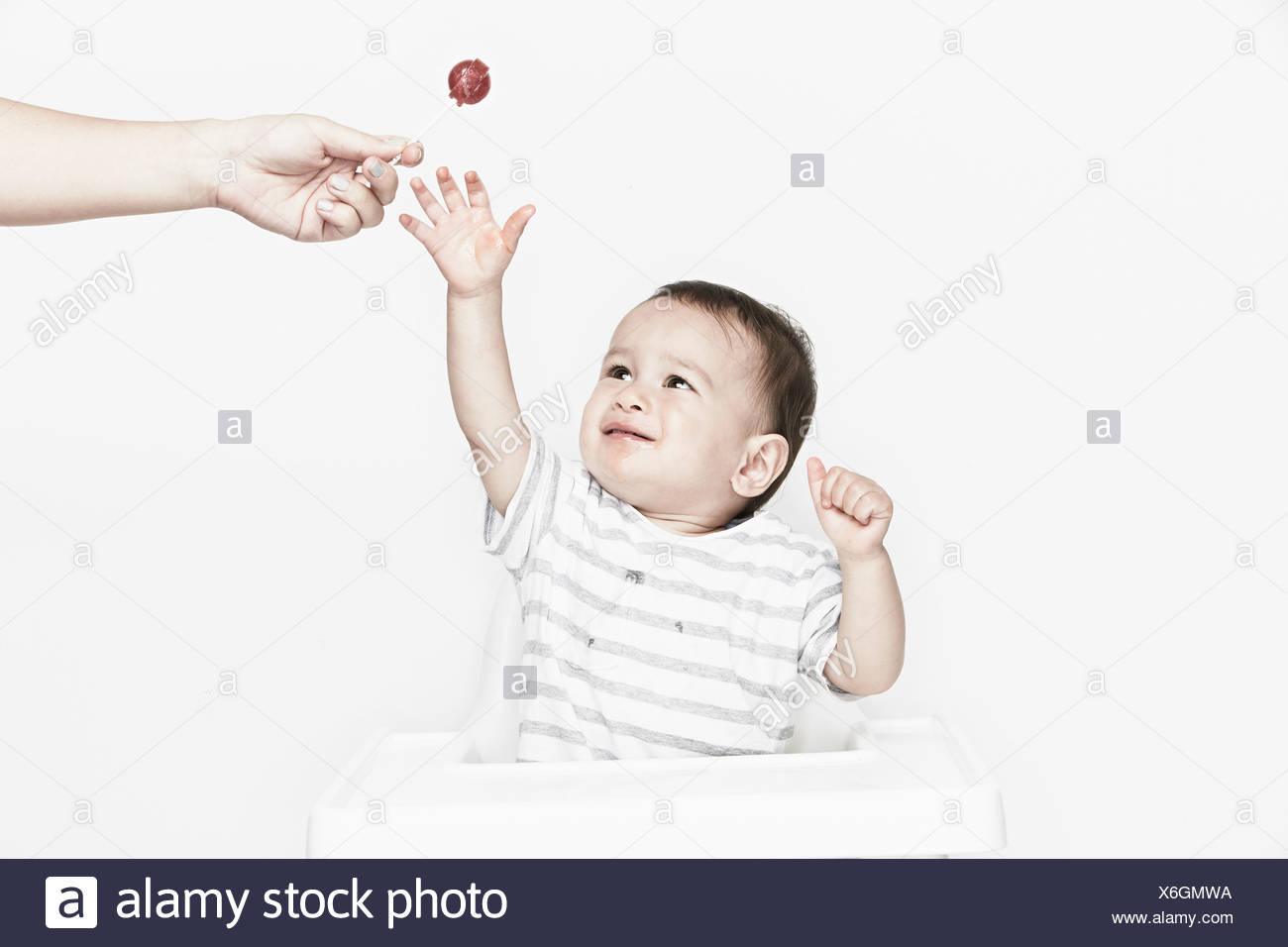 Baby-jungen erreichen für lollipop Stockbild