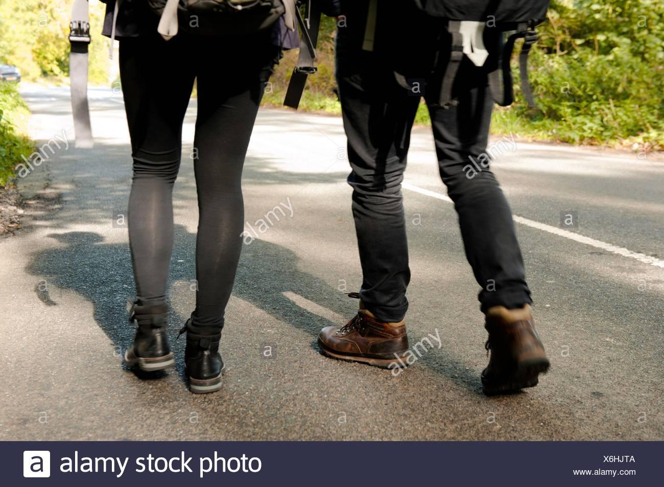 Taille abwärts Rückansicht des jungen Wandern paar auf Landstraße Stockbild