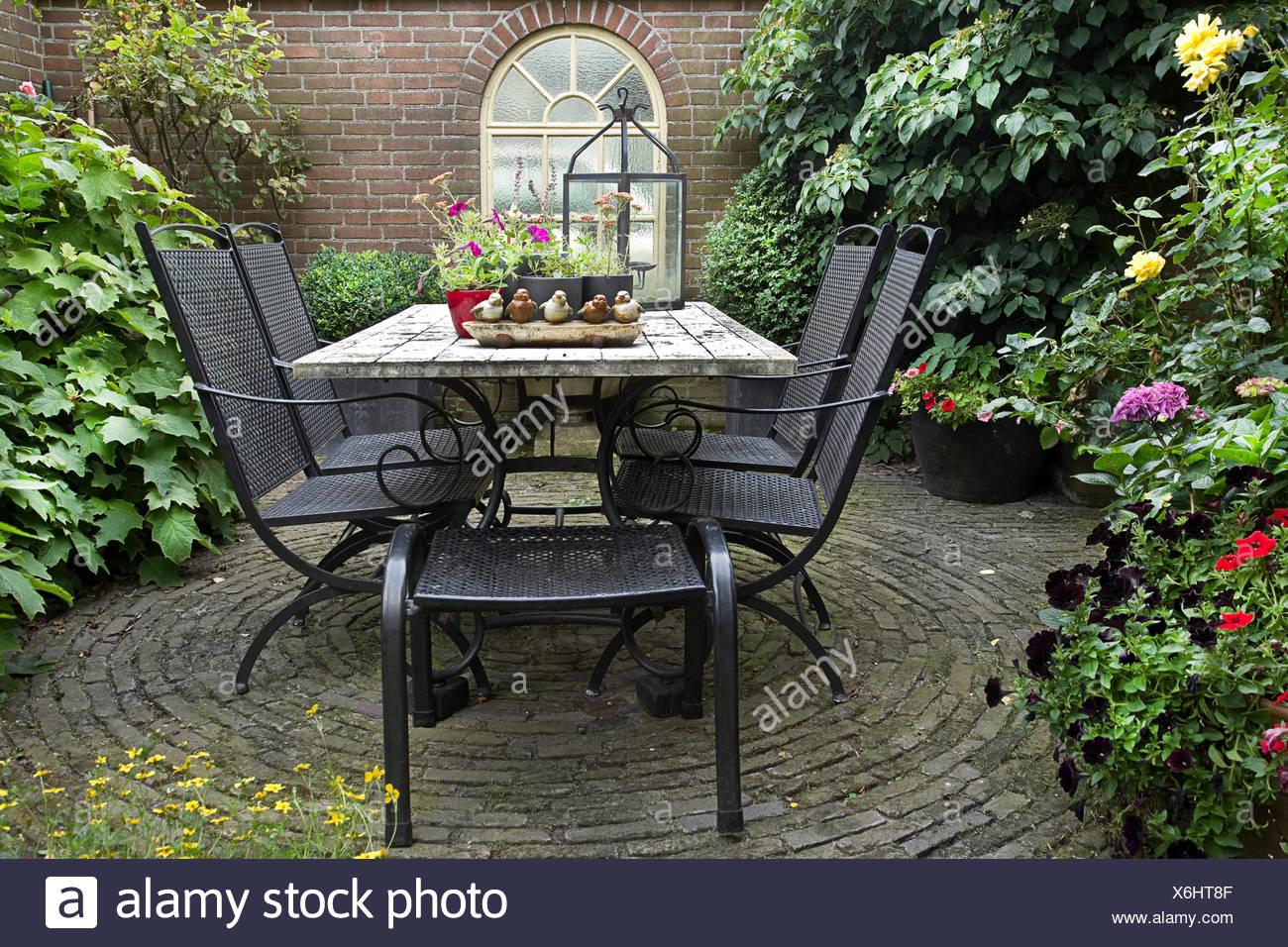 Eisentisch Garten.Geschmiedete Eisentisch Und Stühle Im Garten Mit Blumen