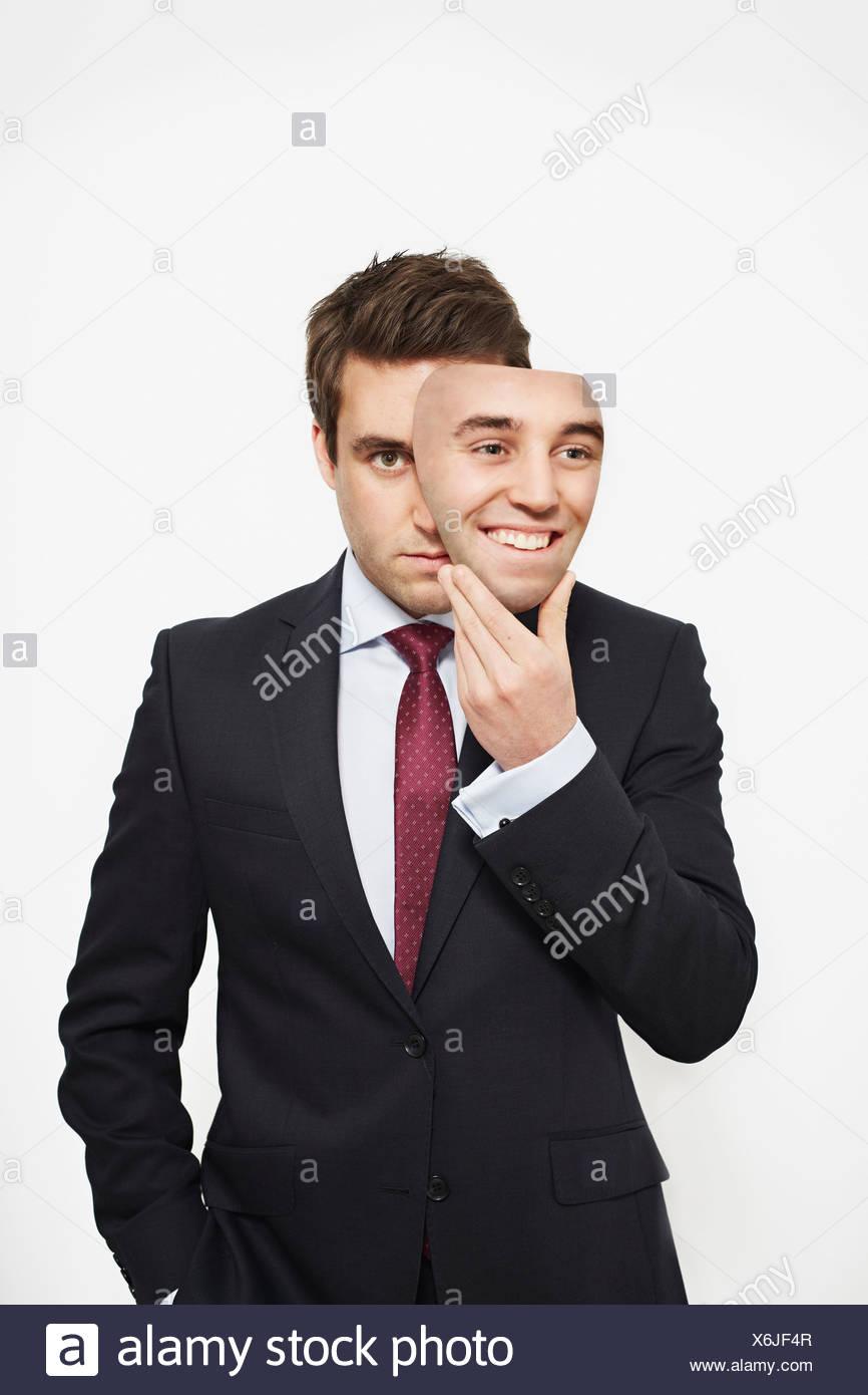 Geschäftsmann, die Maske über seinem Gesicht halten Stockbild
