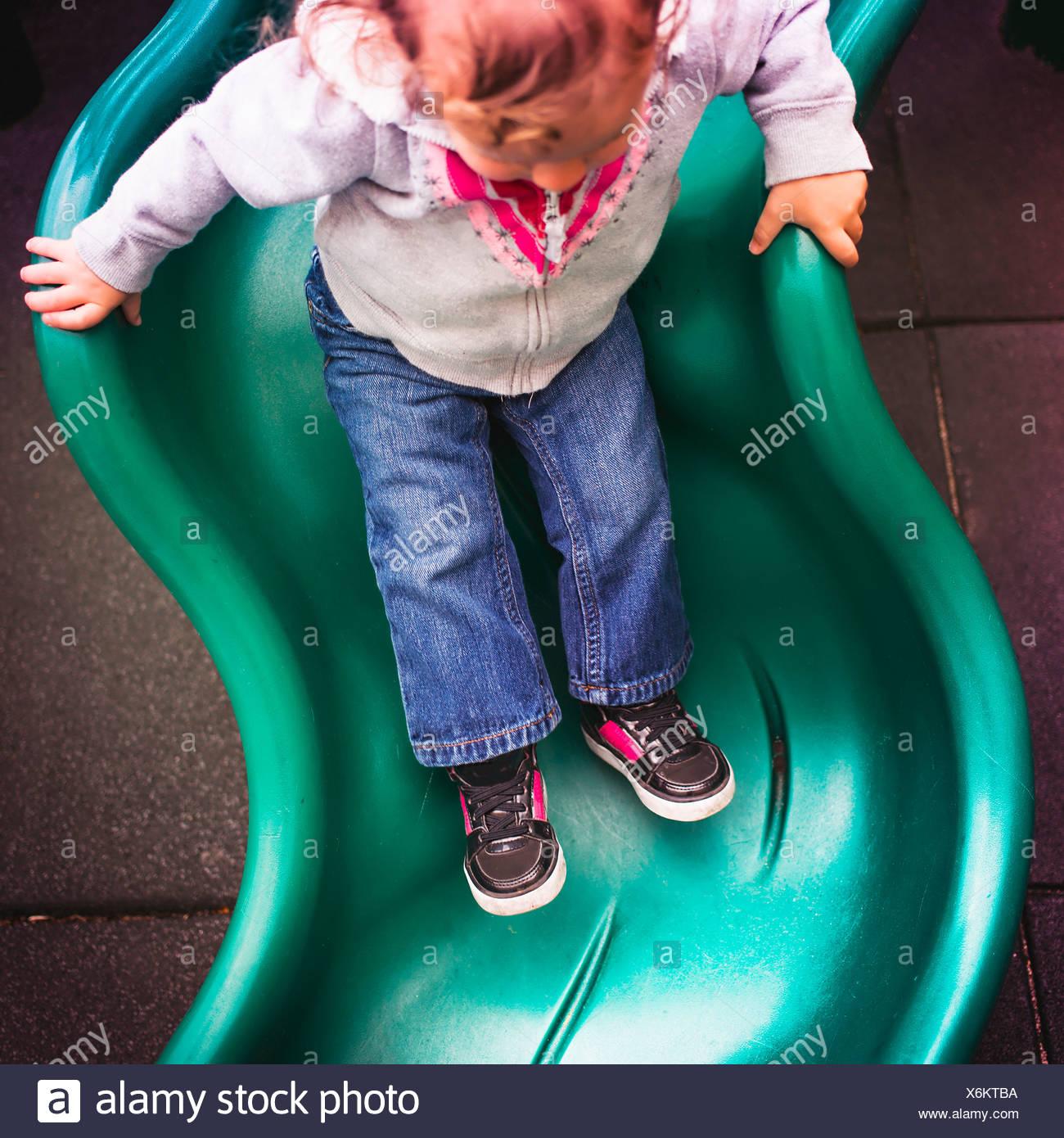 Kleinkind hinunter Folie auf Spielplatz Stockfoto