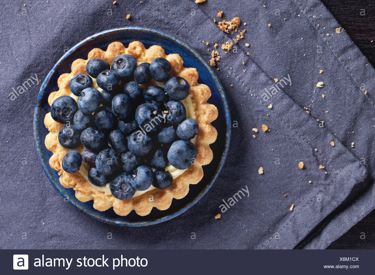 Draufsicht auf Heidelbeer-Tarte auf blaue Keramik-Platte über Textile Serviette serviert. Stockbild