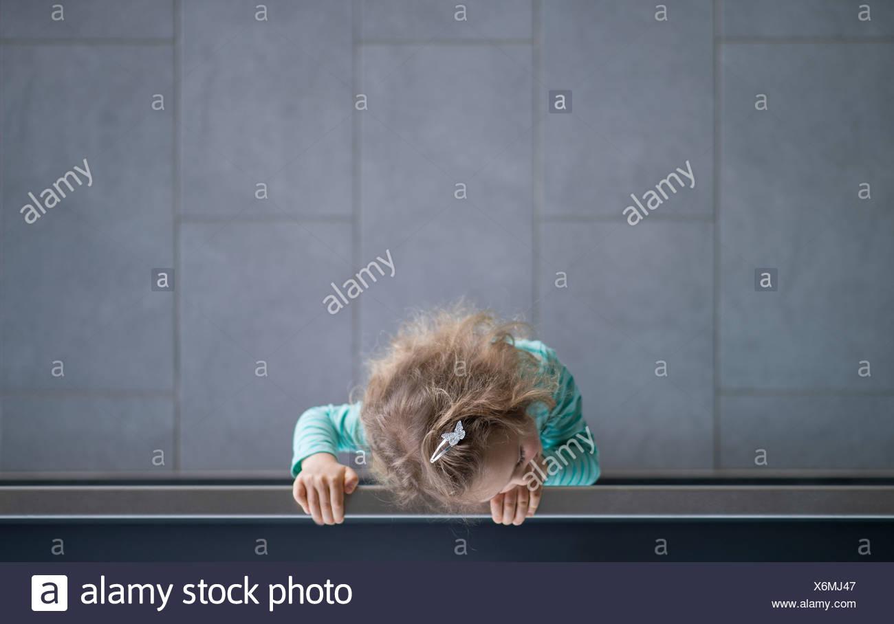 Kleines Mädchen auf der Suche über Geländer, Ansicht von oben Stockbild