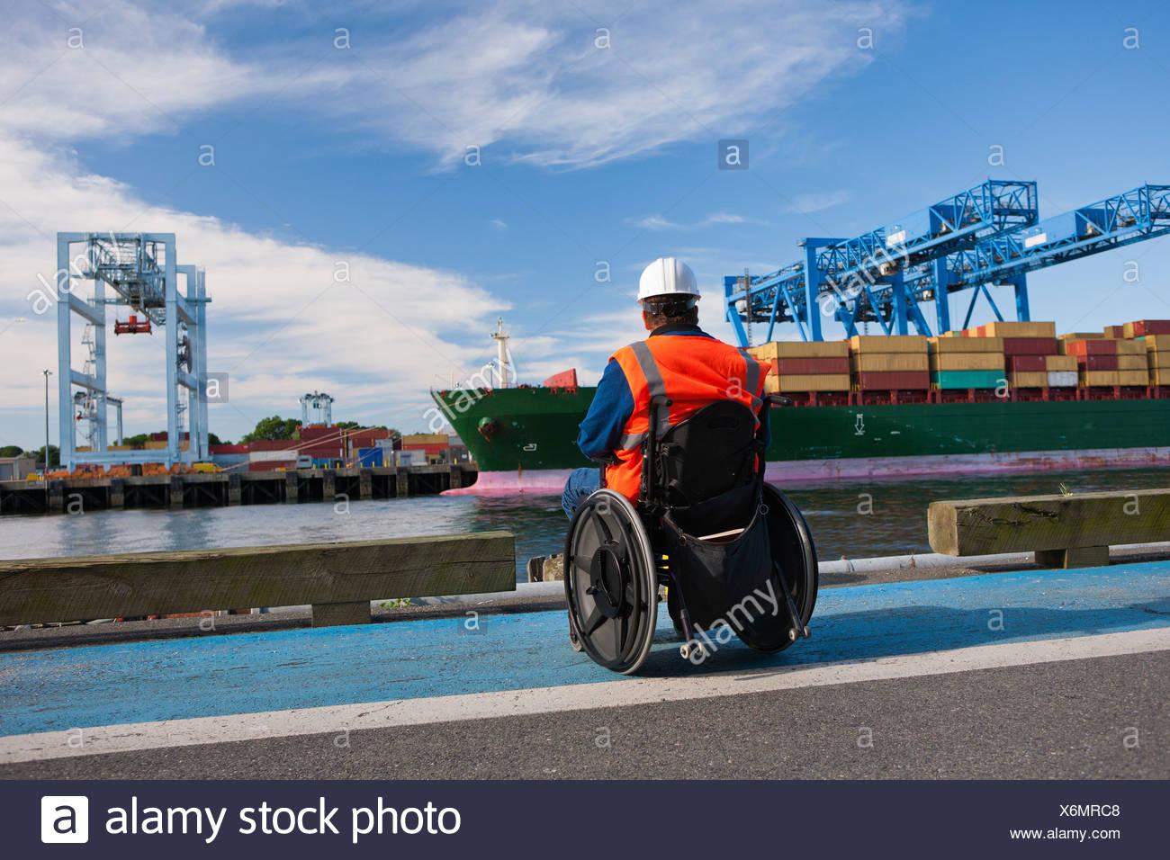 Transport-Ingenieur im Rollstuhl Inspektion Container-Schiff im Verschiffungshafen Stockbild