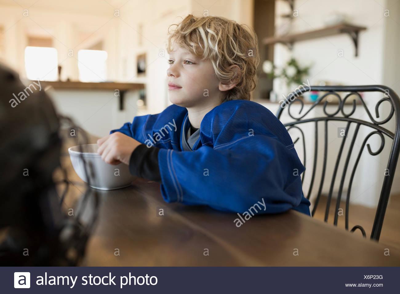 Nachdenkliche junge essen Müsli am Tisch Stockbild