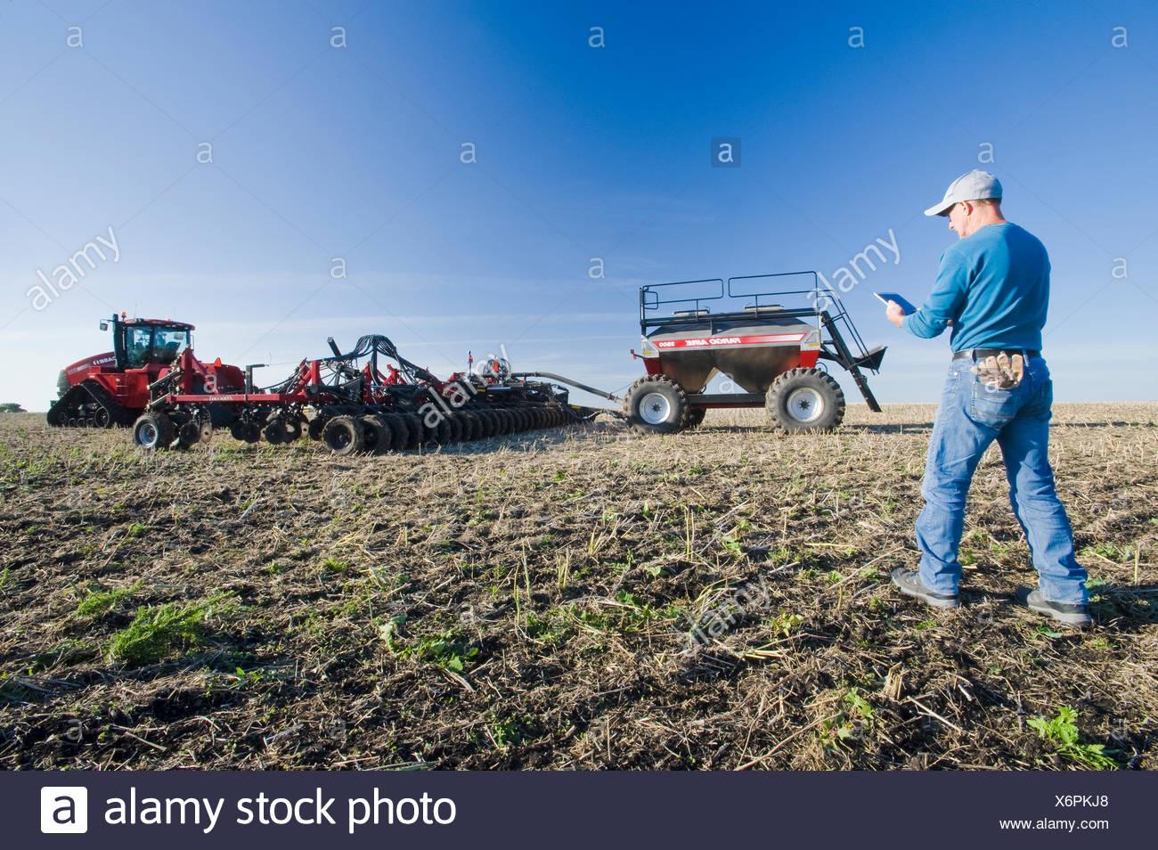 Landwirt mit einem Tablet vor einem Traktor und pneumatische Sämaschine Aussaat Winterweizen in einem Null bis Feld mit Raps Stoppeln, in der Nähe von lorette, Manitoba, Kanada Stockbild