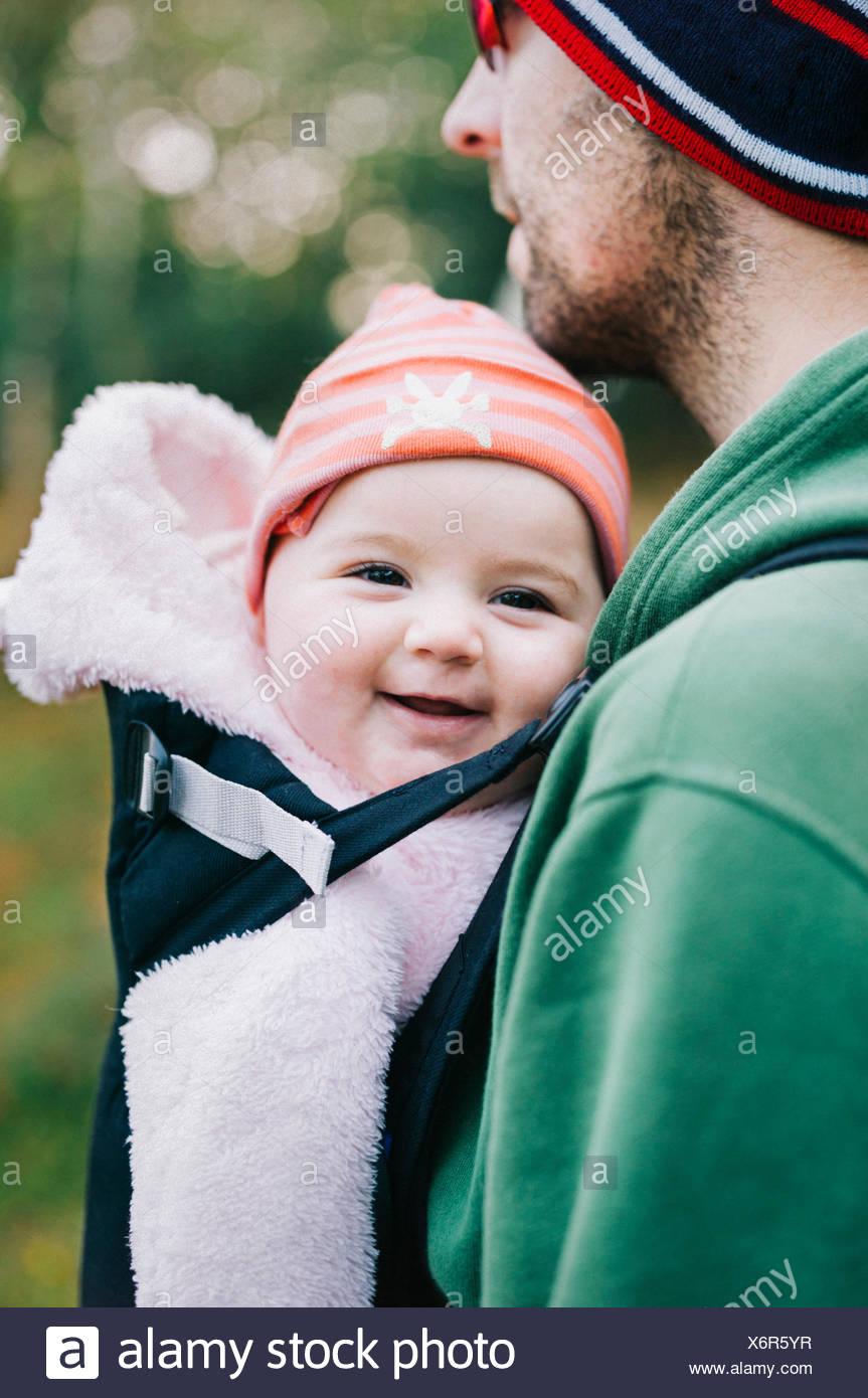 Ein Baby in einer Schlinge, die von ihrem Vater im Freien im Winter getragen werden. Stockbild