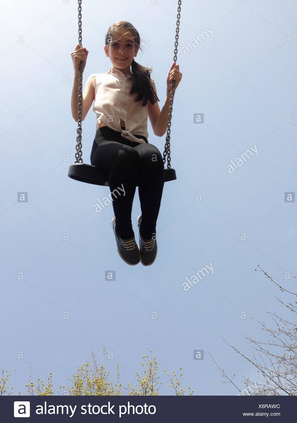 Mädchen auf einer Schaukel sitzend Stockbild