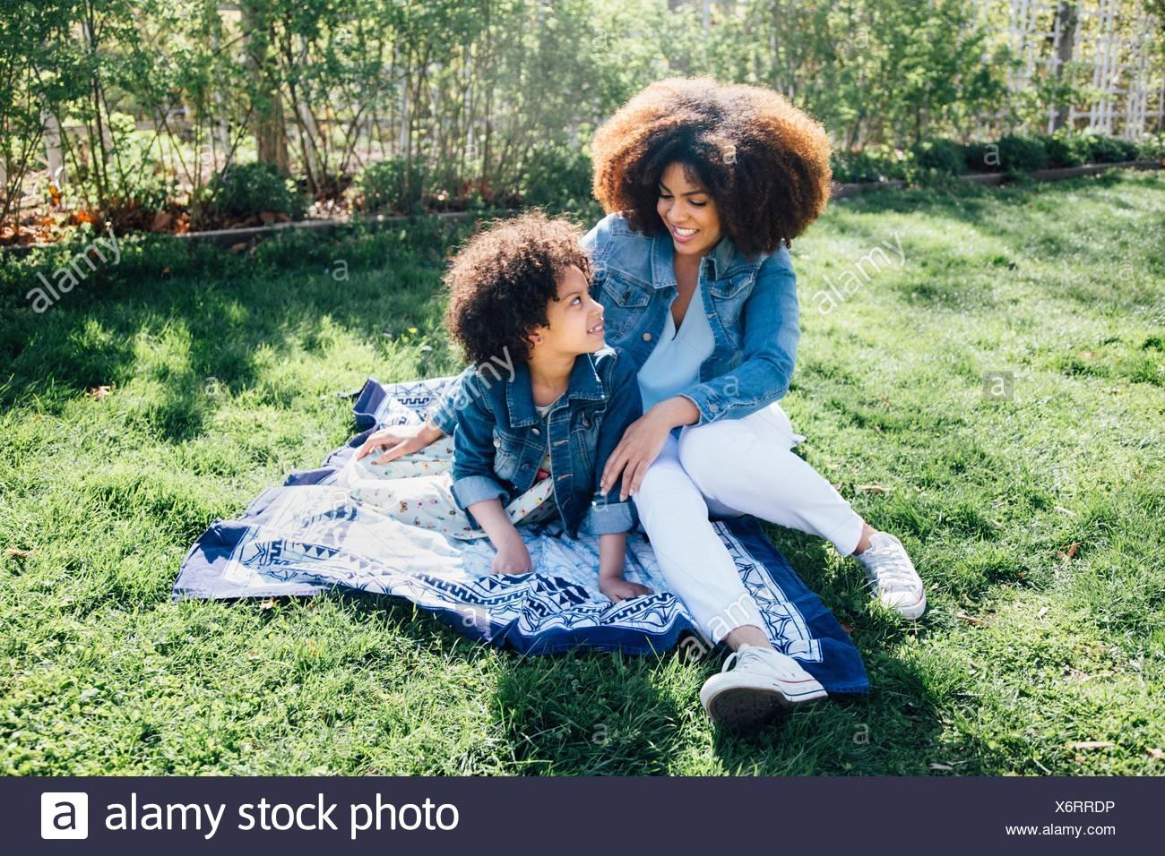 Mutter mit Arm um Tochter sitzen auf Decke Stockbild