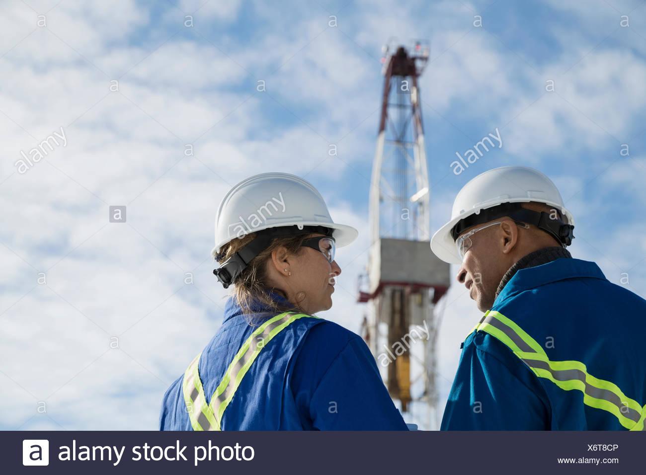 Arbeitnehmer, die unter Bohrinsel im Gespräch Stockbild