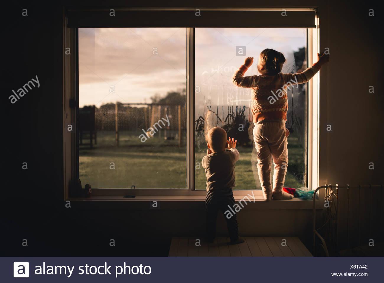 Jungen und Mädchen auf das Fenster im Morgen Kondensation Stockbild