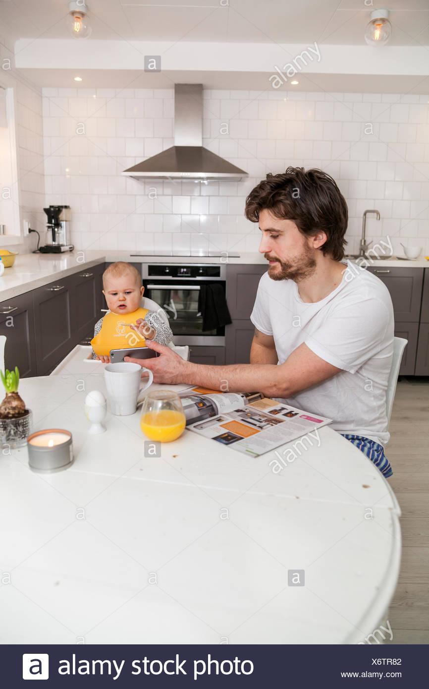 Schweden, Vater und Sohn (12-17 Monate) sitzen in der Küche Stockbild