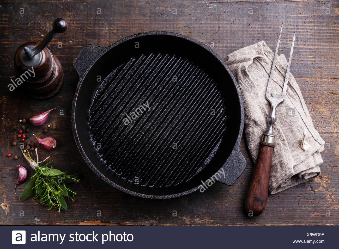 Schwarzes Eisen leeren Grillpfanne und Fleisch Gabel auf Holz Textur Hintergrund Stockbild