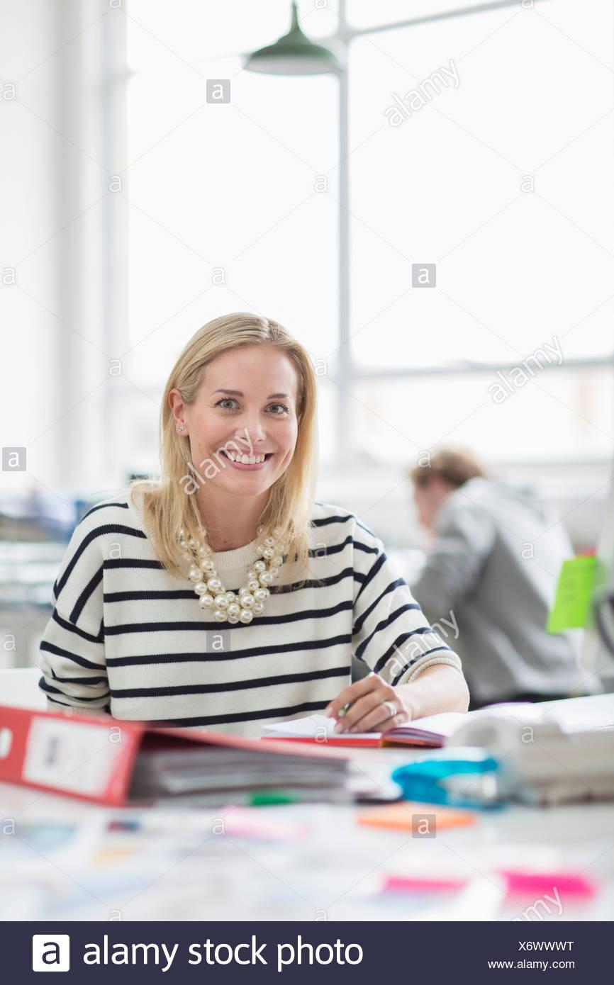 Junge Frau sitzt am Schreibtisch und lächelnd in Kreativbüro, Porträt Stockbild