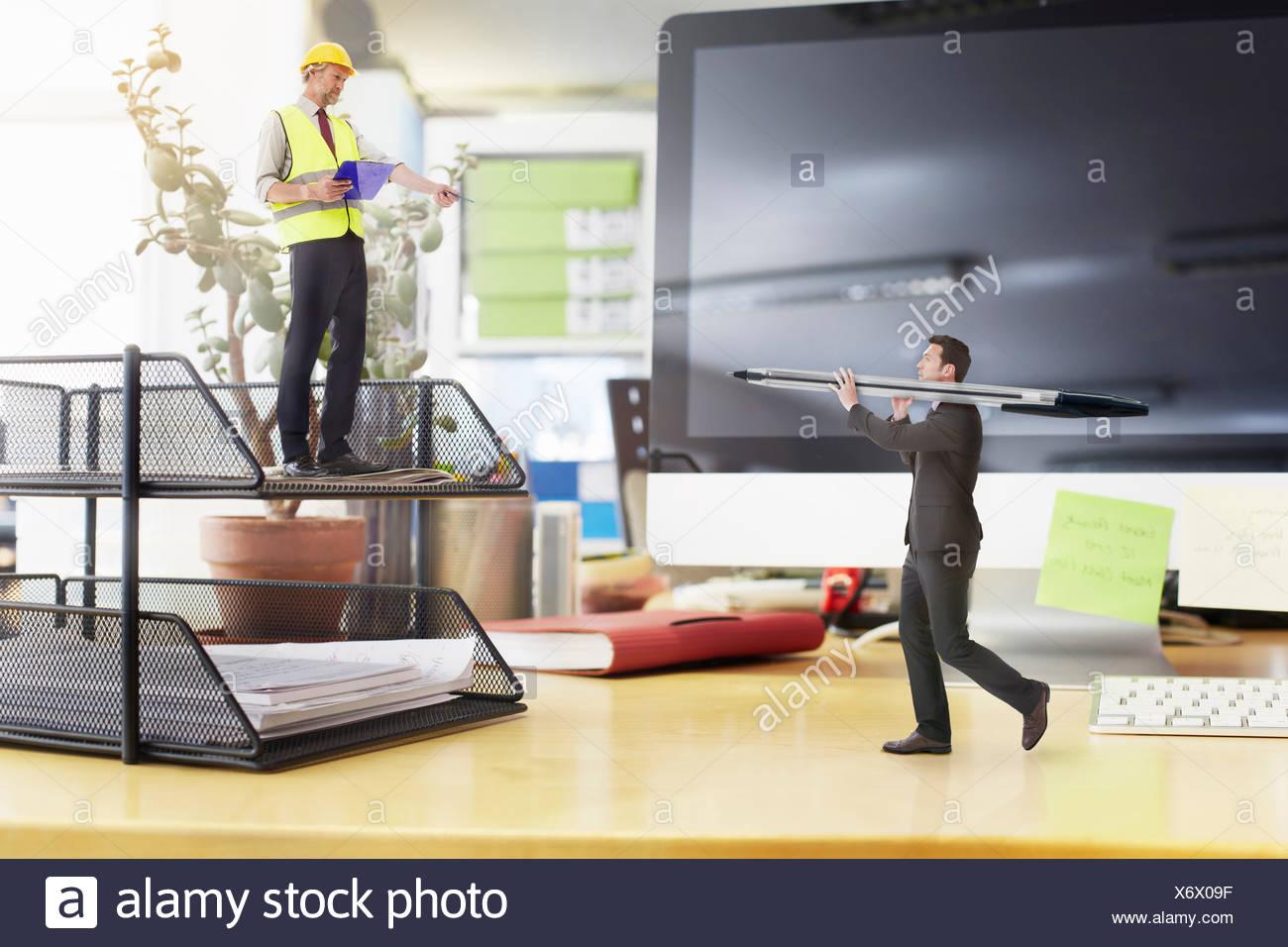 Reife Vorarbeiter Regie Geschäftsmann mit großen Stift auf übergroße Schreibtisch Stockbild