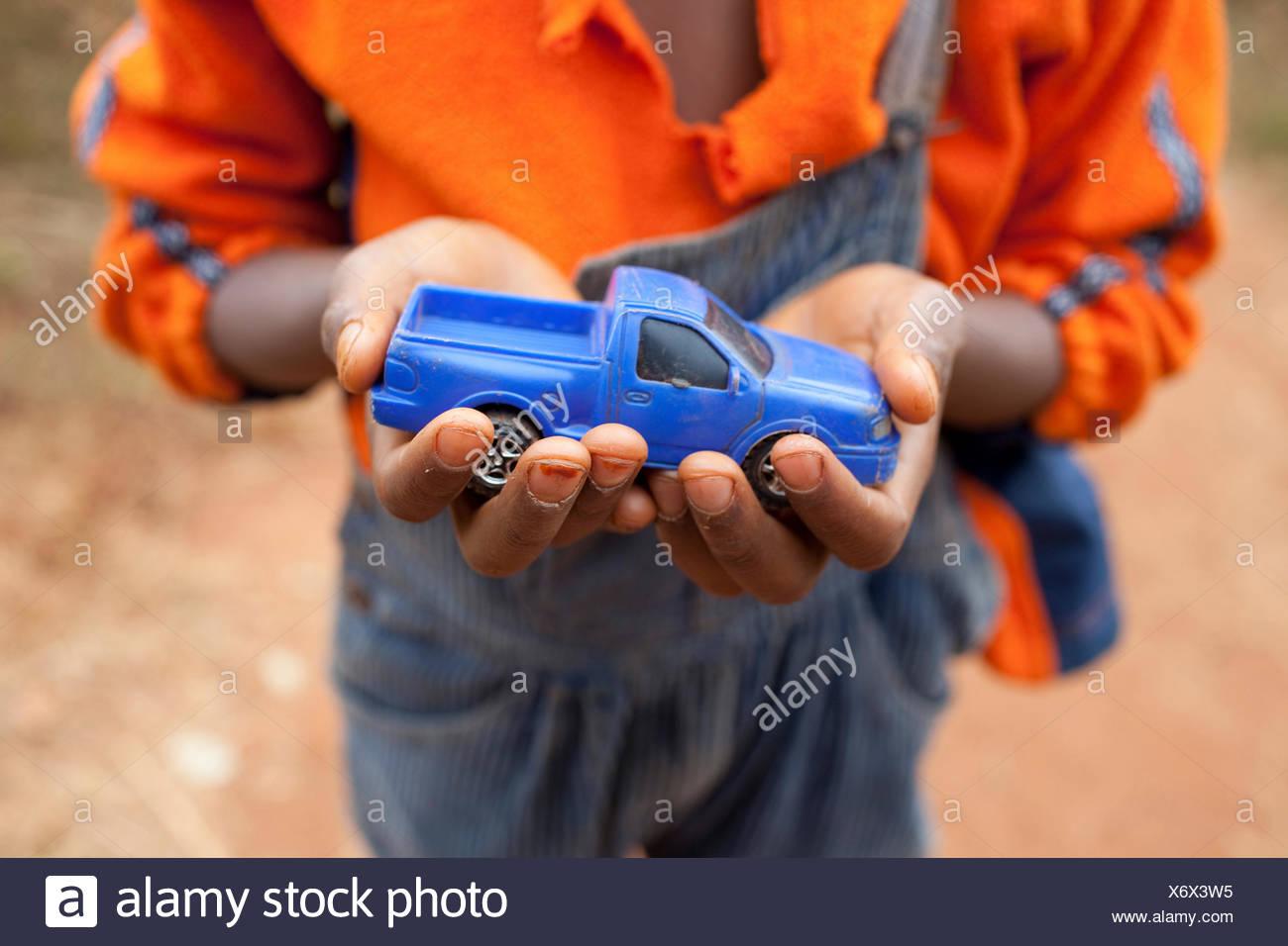 Junge mit einem blauen Spielzeugauto in den Händen, Burundi, Karuzi, Buhiga Stockbild
