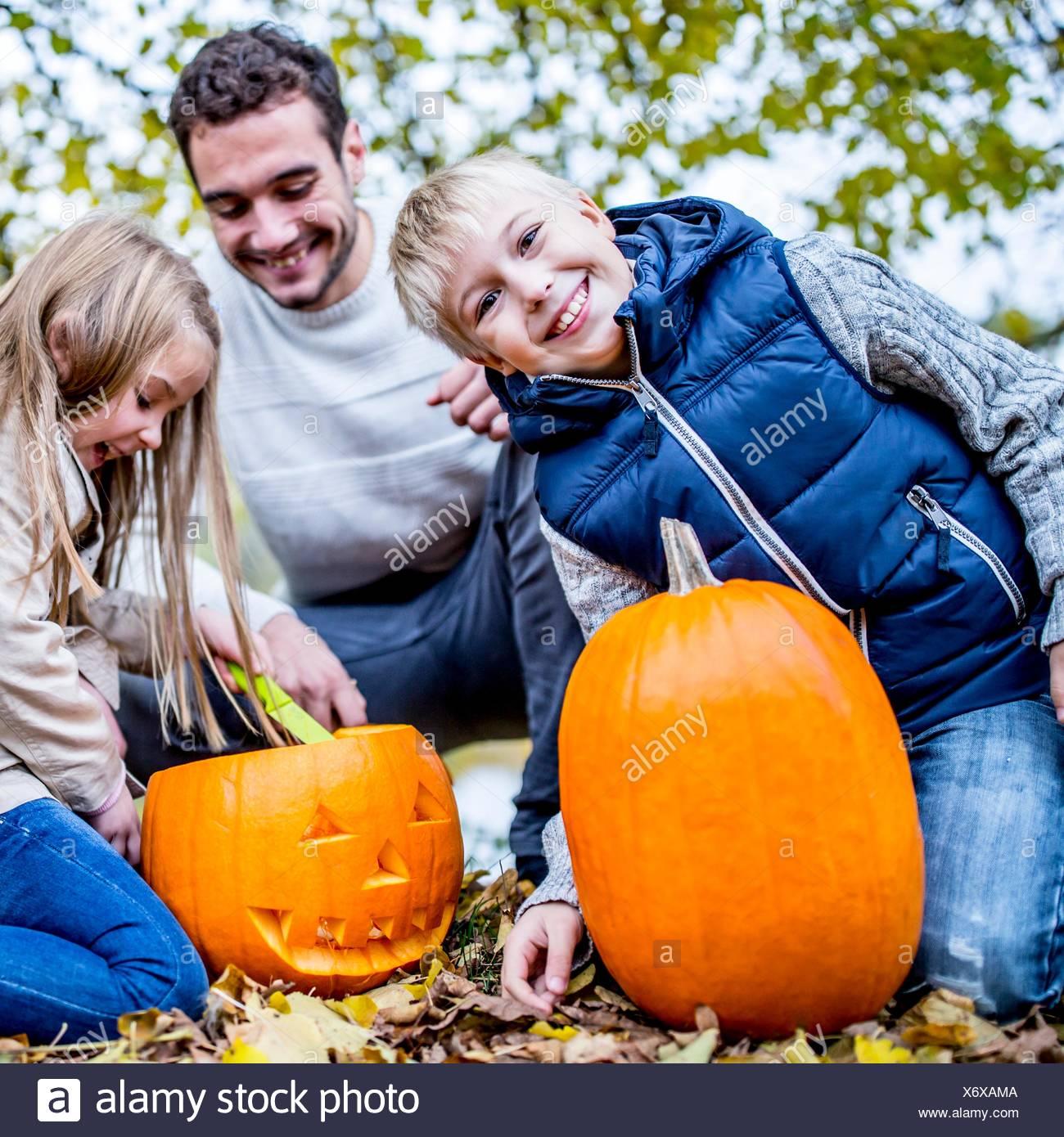 -MODELL VERÖFFENTLICHT. Familie machen Halloween-Kürbis. Stockbild