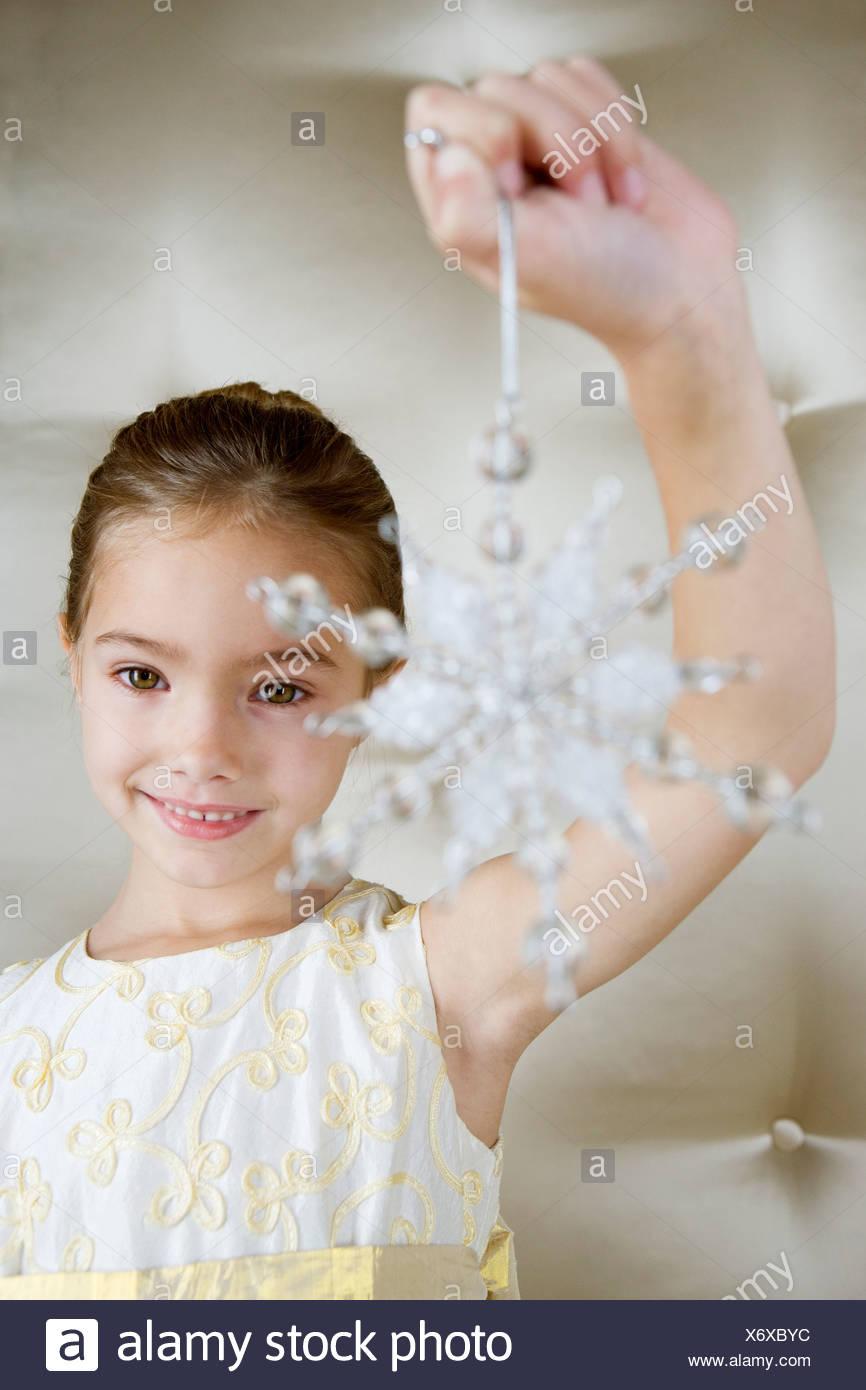 Junges Mädchen in einem Partykleid hält eine Weihnachts-Dekoration Stockbild
