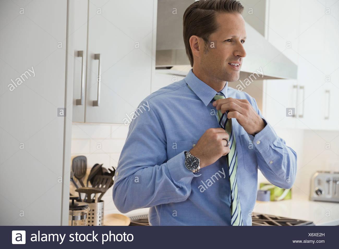 Geschäftsmann binden Krawatte in Küche Stockbild