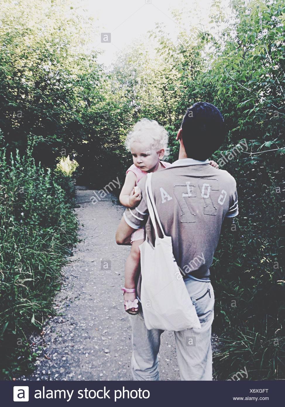 Rückansicht des Mann, Baby und Tasche zu Fuß auf dem Gehweg inmitten von Bäumen im Park Stockbild