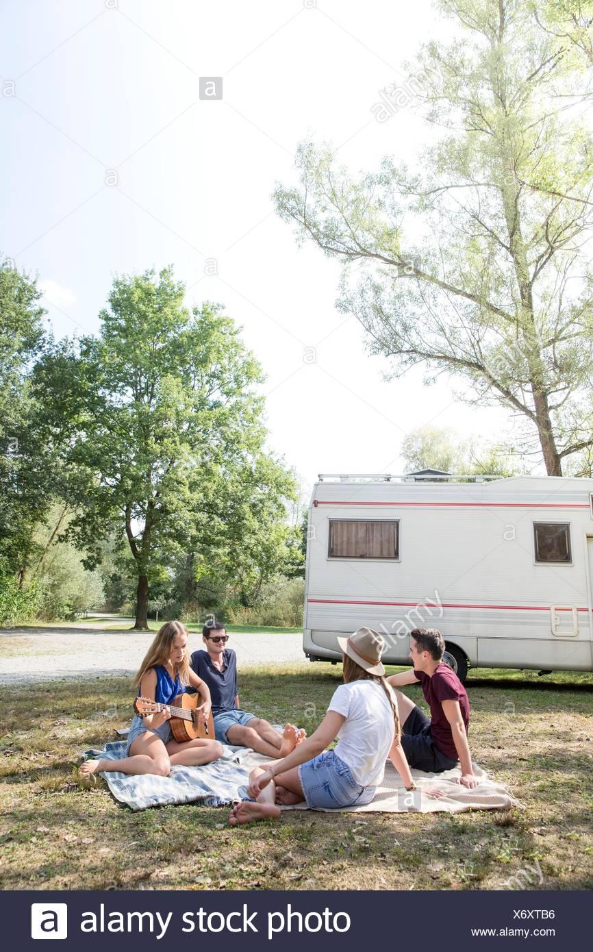 Gruppe junger Erwachsener auf der Picknickdecke sitzen, relaxen, Wohnmobil im Hintergrund Stockbild
