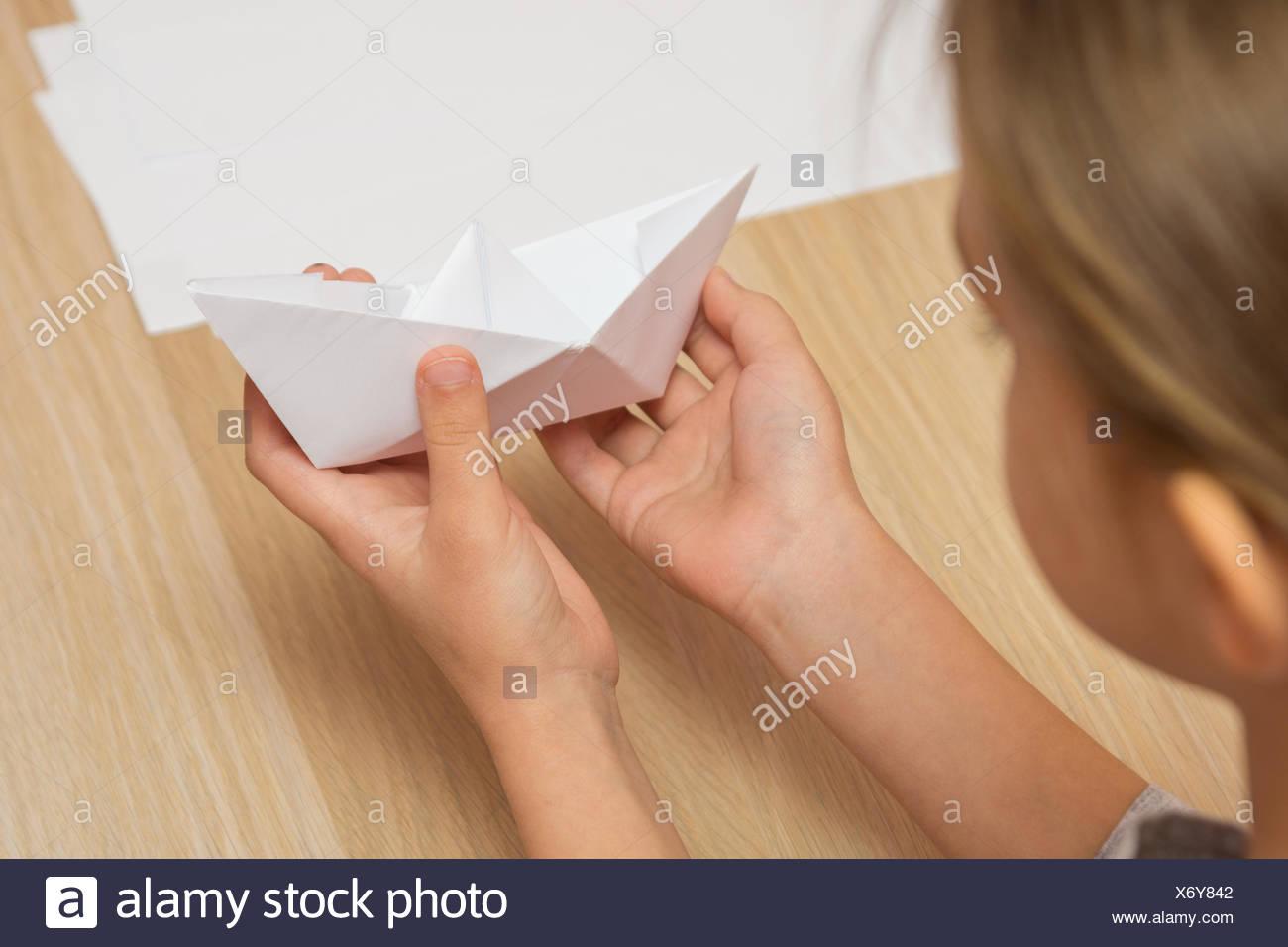 Eine Mädchen schaut auf ein Papierschiff von hand gefertigt Stockfoto