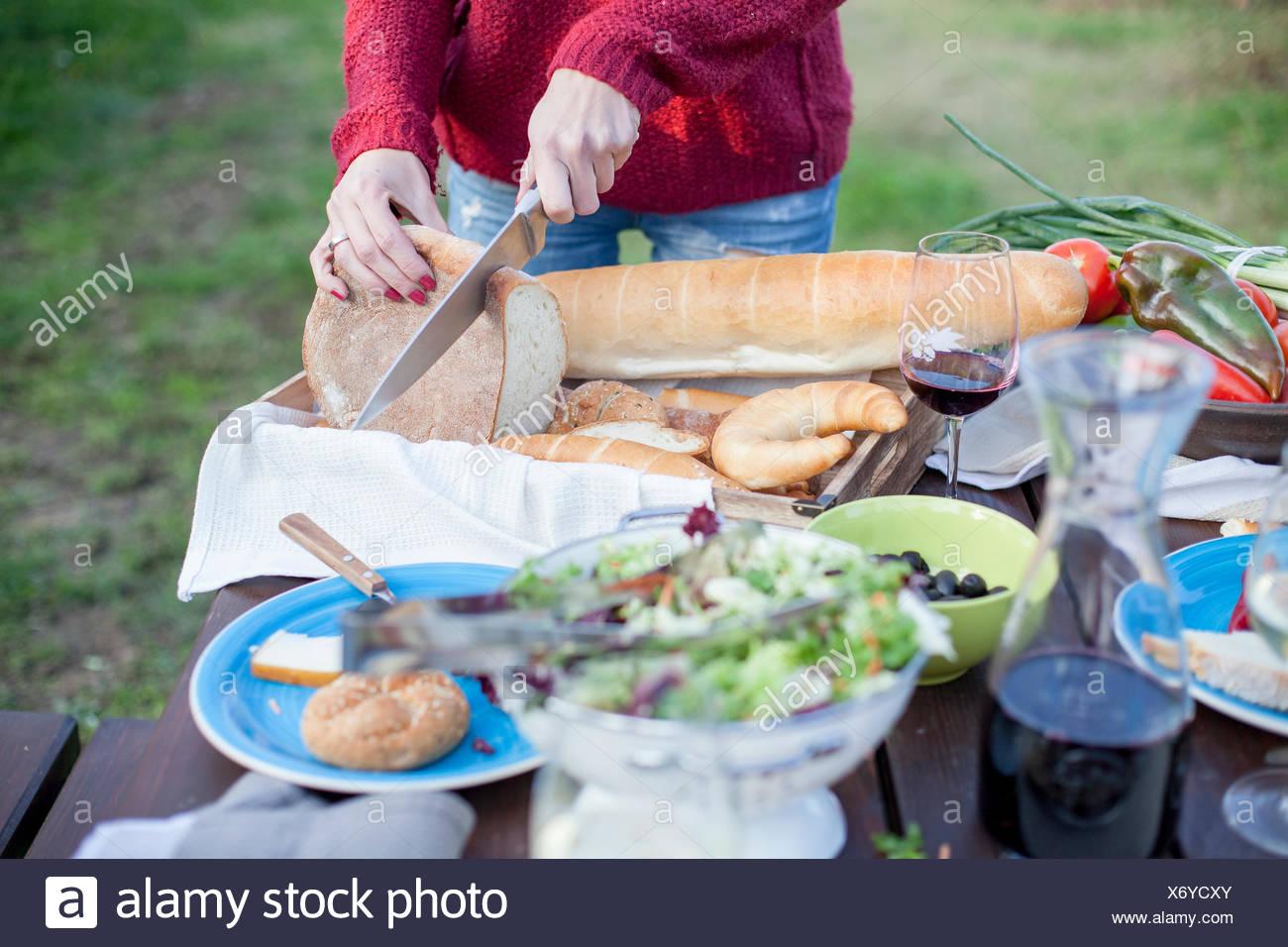 Person auf Gartenparty Laib Brot schneiden Stockfoto