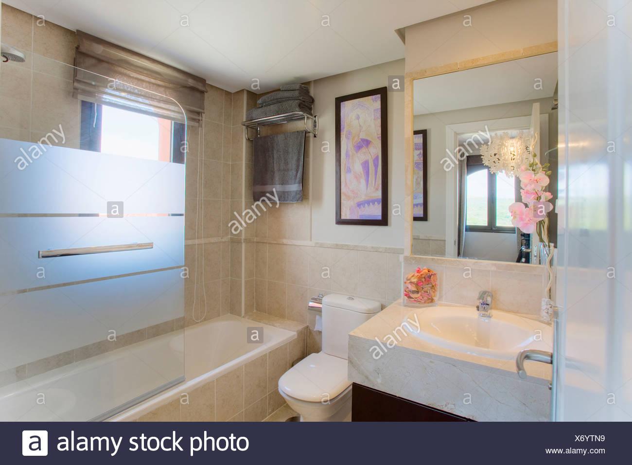 Kleines modernes Bad mit Spiegel über dem Waschbecken und opakem ...