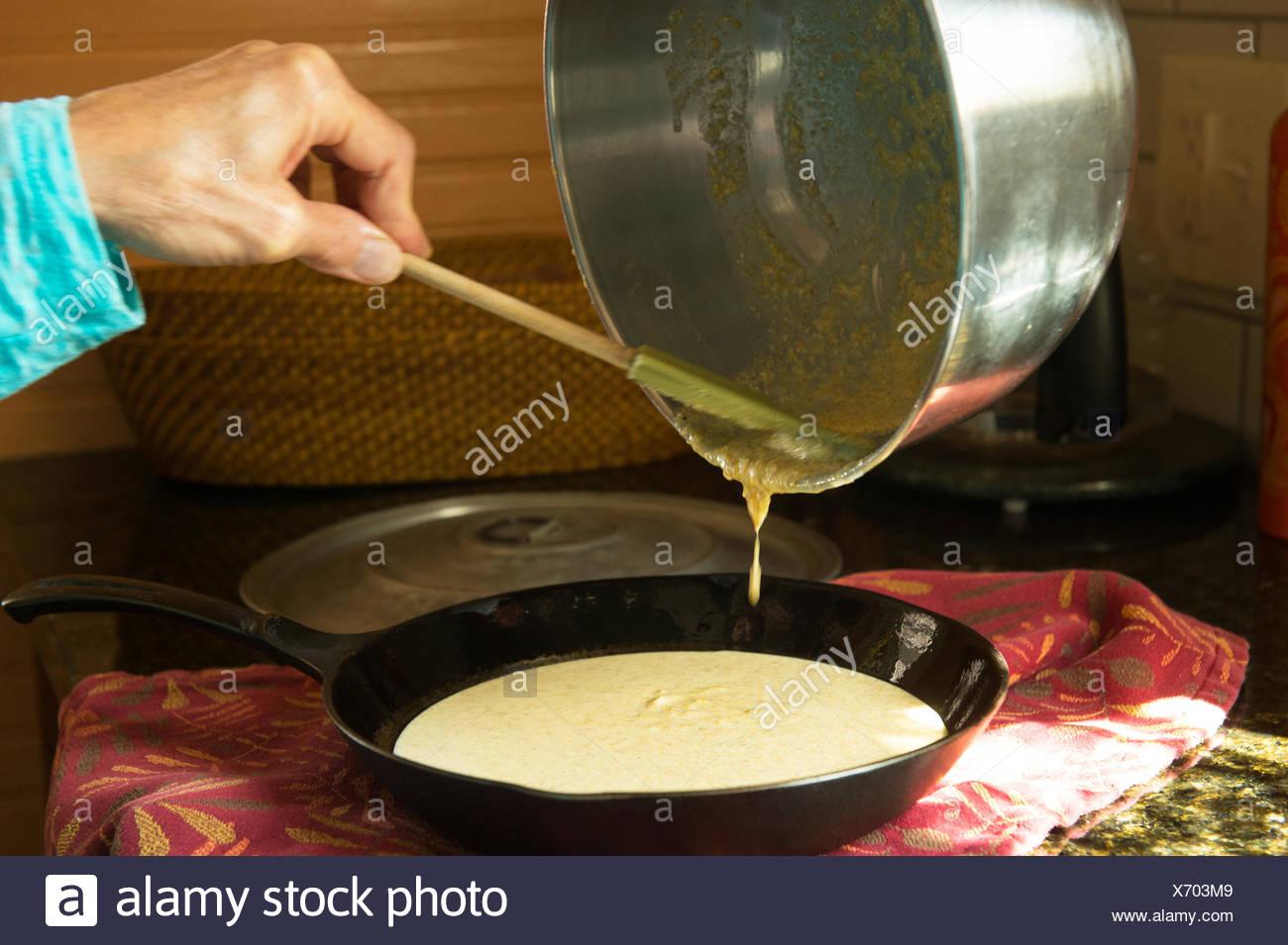 Eine Person, die Zubereitung von Speisen in einer gusseisernen Pfanne erhitzen. Stockbild
