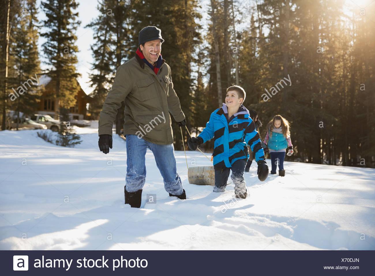 Vater und Sohn ziehen Rodeln im Schnee Stockbild