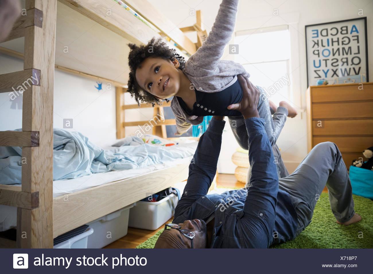 Vater heben fliegenden Tochter im Schlafzimmer Stockbild