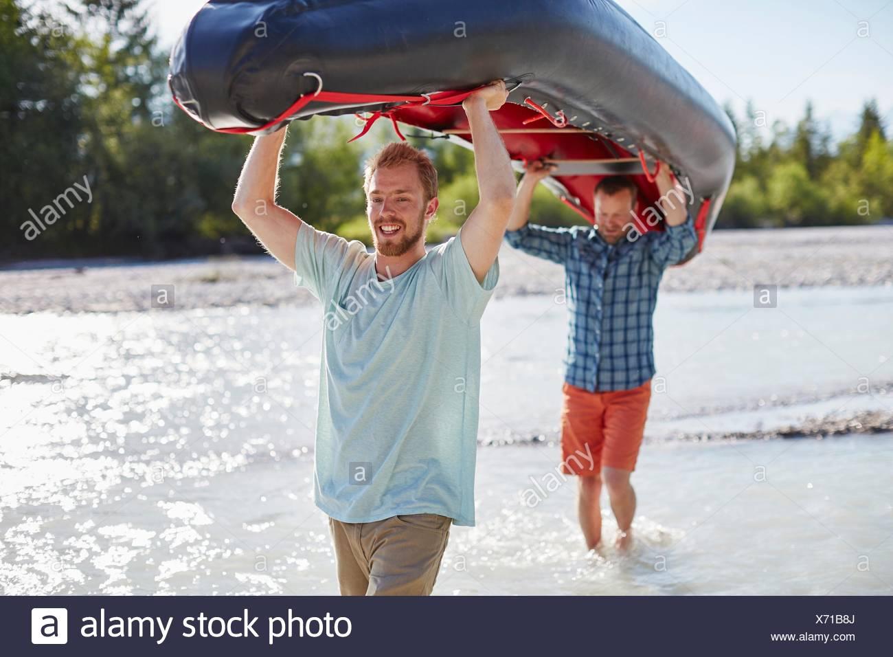 Zwei Männer tragen Jolle über ihren Köpfen durch flaches Wasser Stockbild
