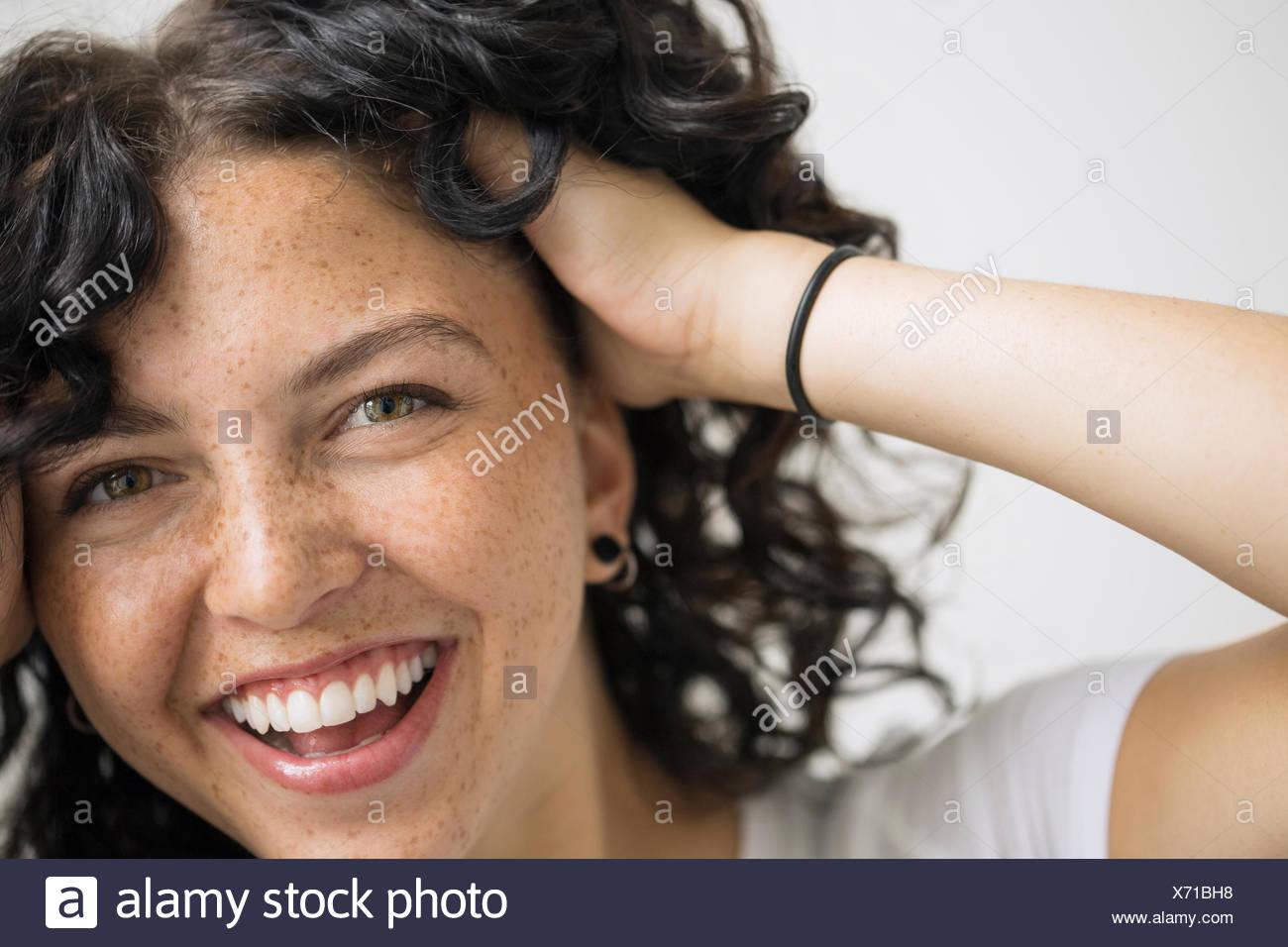 Porträt der lächelnde Frau mit Händen in Haar Stockbild