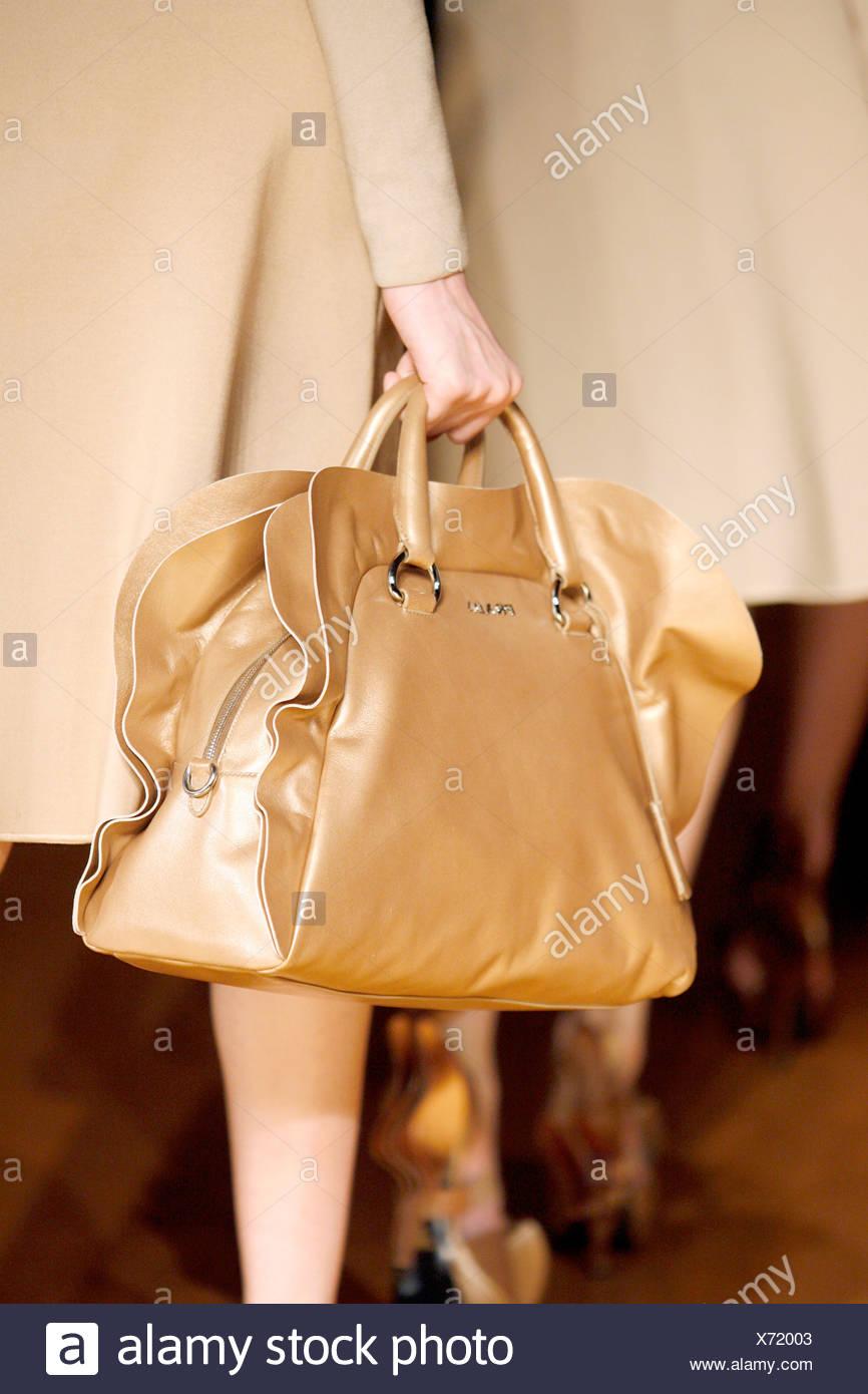 17ac8a15881c0 Prada Mailand bereit zu tragen Herbst Wintermodell trägt einen  beigefarbenen Mantel und hält eine beiges Lederhandtasche mit Volants