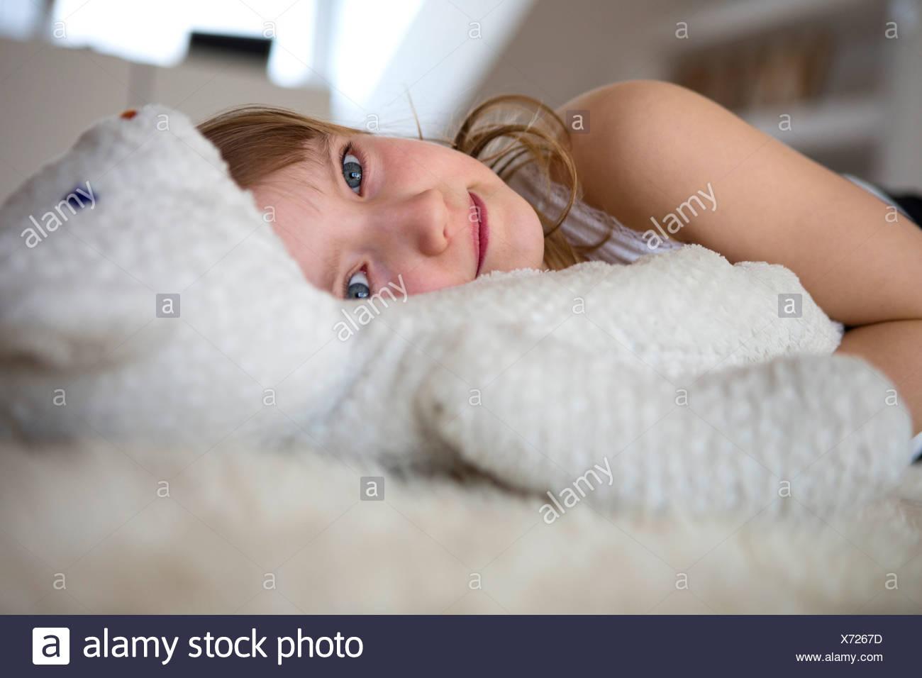 Mädchen mit Teddybär auf pelzigen Bett liegend Stockbild