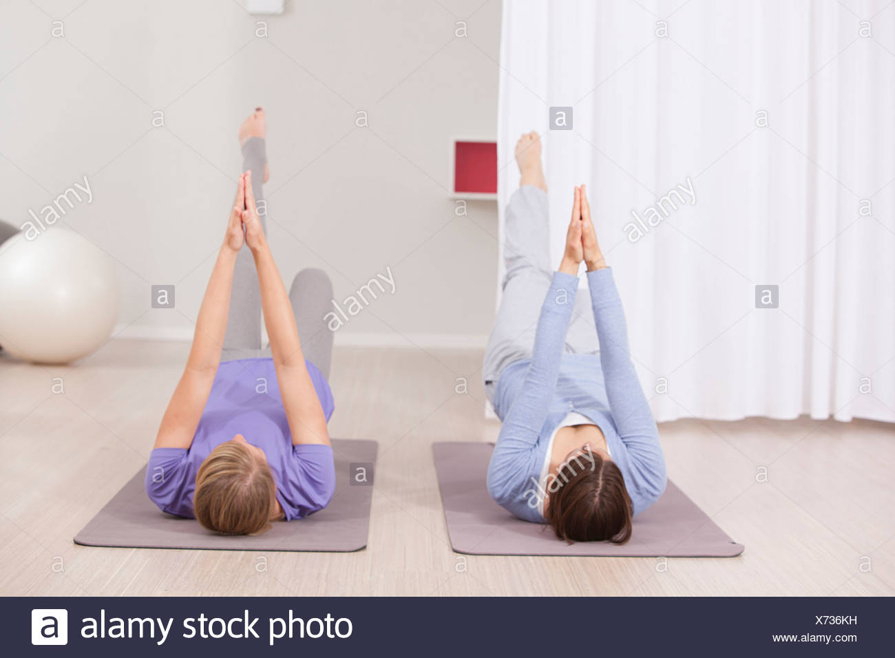 Frauen, die Pilates-Übung mit gefalteten Händen Stockbild