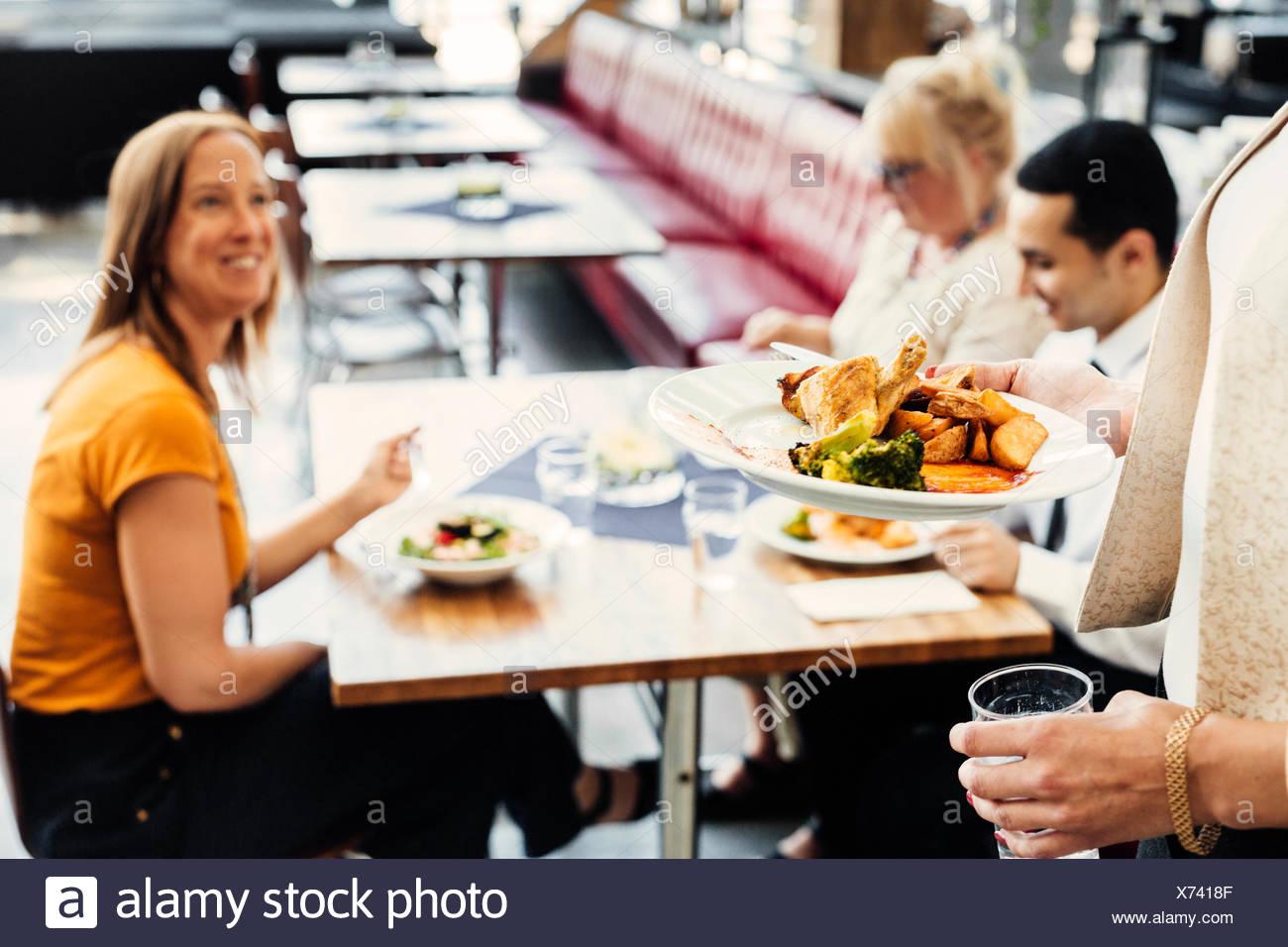Vier Kollegen treffen beim Mittagessen in der Cafeteria Stockfoto