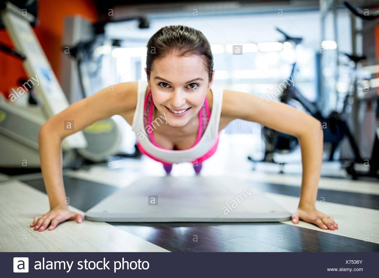 EIGENTUM FREIGEGEBEN. -MODELL VERÖFFENTLICHT. Porträt der jungen Frau Liegestütz im Fitness-Studio zu tun. Stockbild
