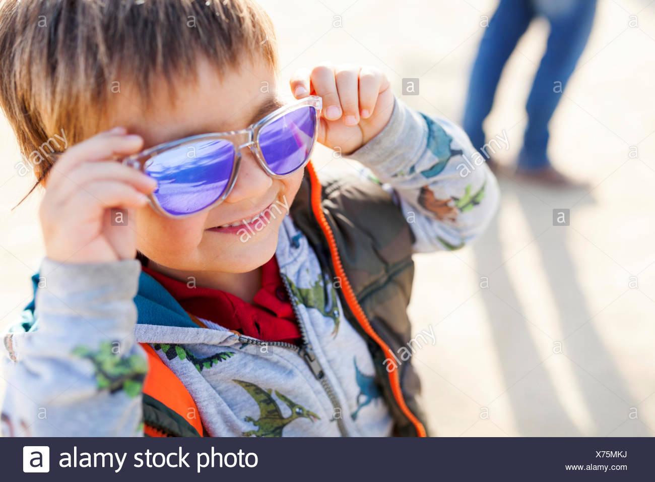 Porträt von lächelnden kleinen Jungen, die farbige Sonnenbrille aufsetzen Stockbild
