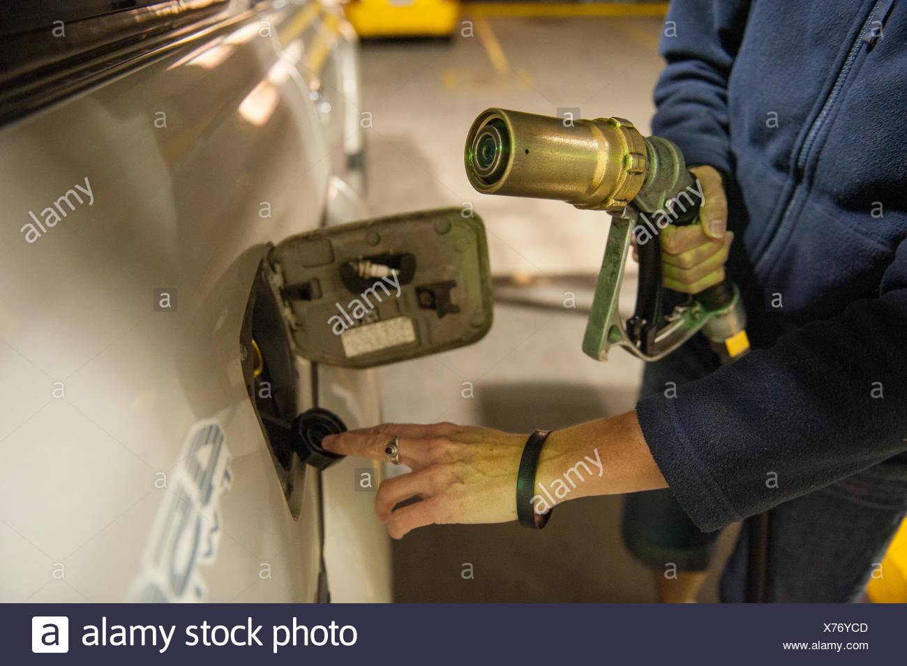 Eine Frau füllt sich ihr Fahrzeug mit verflüssigtem Erdgas. Stockbild