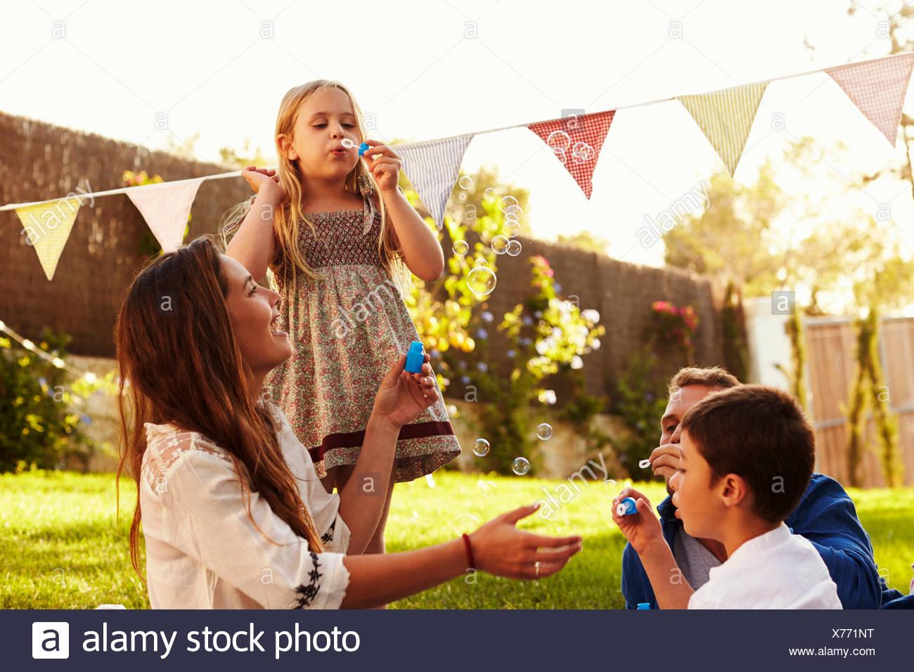 Eltern, die Seifenblasen mit Kindern im Garten Stockbild