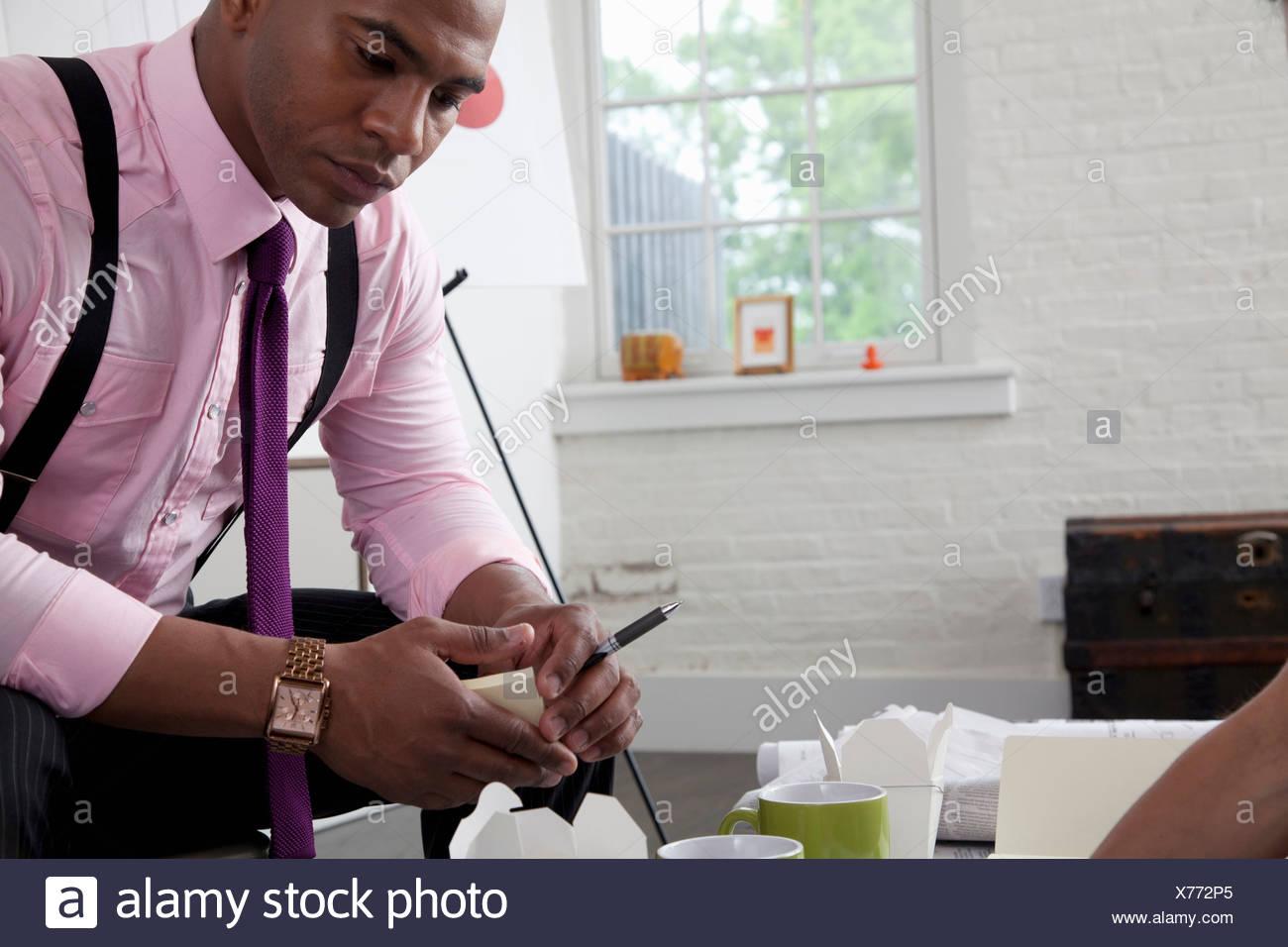 Mitte adult Büroangestellter blickte auf Papierkram auf Tisch Stockbild